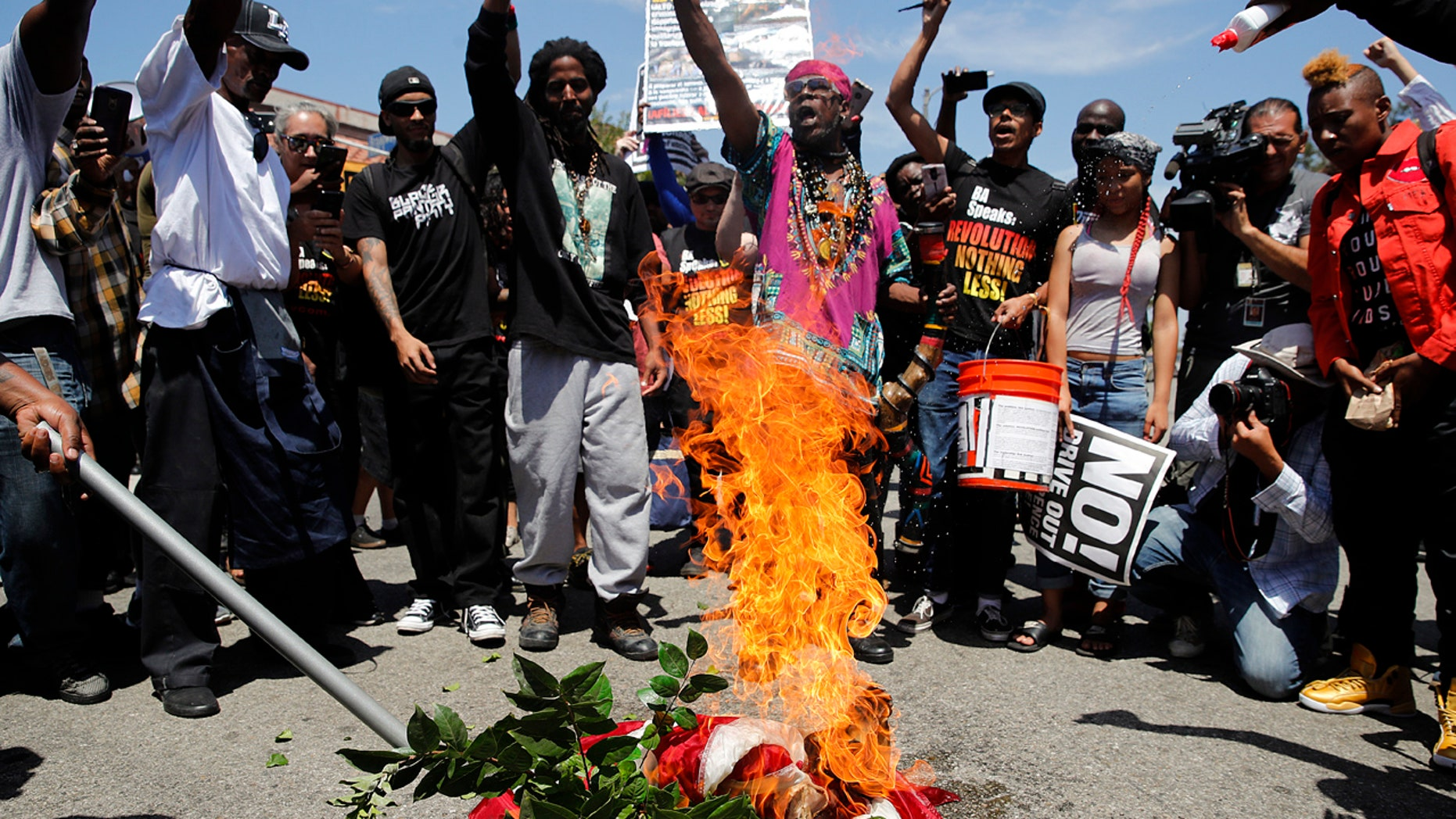 People chant slogans as they burn a U.S. flag outside the Los Angeles office of U.S. Rep. Maxine Waters, Thursday, July 19, 2018, in Los Angeles.