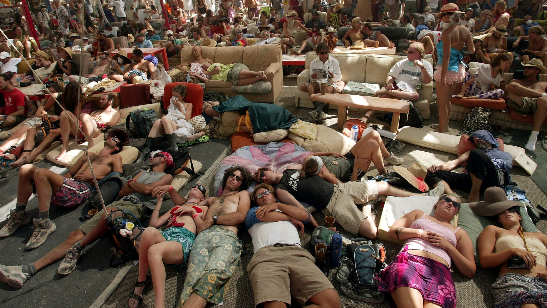 People seek shelter and rest inside the Center Camp Cafe at the Burning Man Festival in Black Rock City, Nevada, August 28, 2003. The Burning Man Festival has been celebrated annually since 1986 and draws around 20,000 people to the Black Rock Desert, celebrating radical self expression. - RTXM6VH