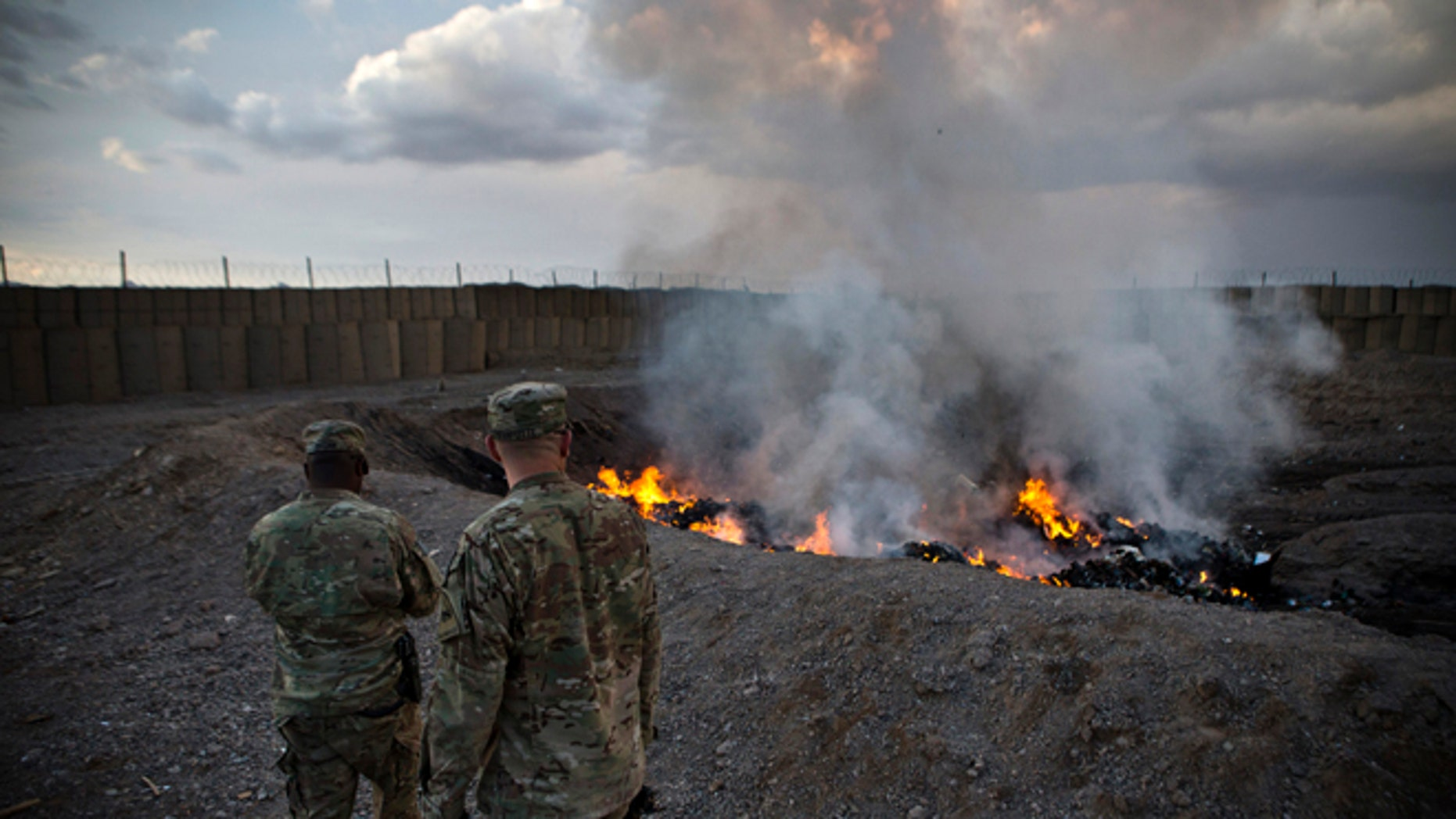 February 4, 2013: U.S. Army soldiers watch garbage burn in a burn-pit at Forward Operating Base Azzizulah in the Kandahar Province of Afghanistan.