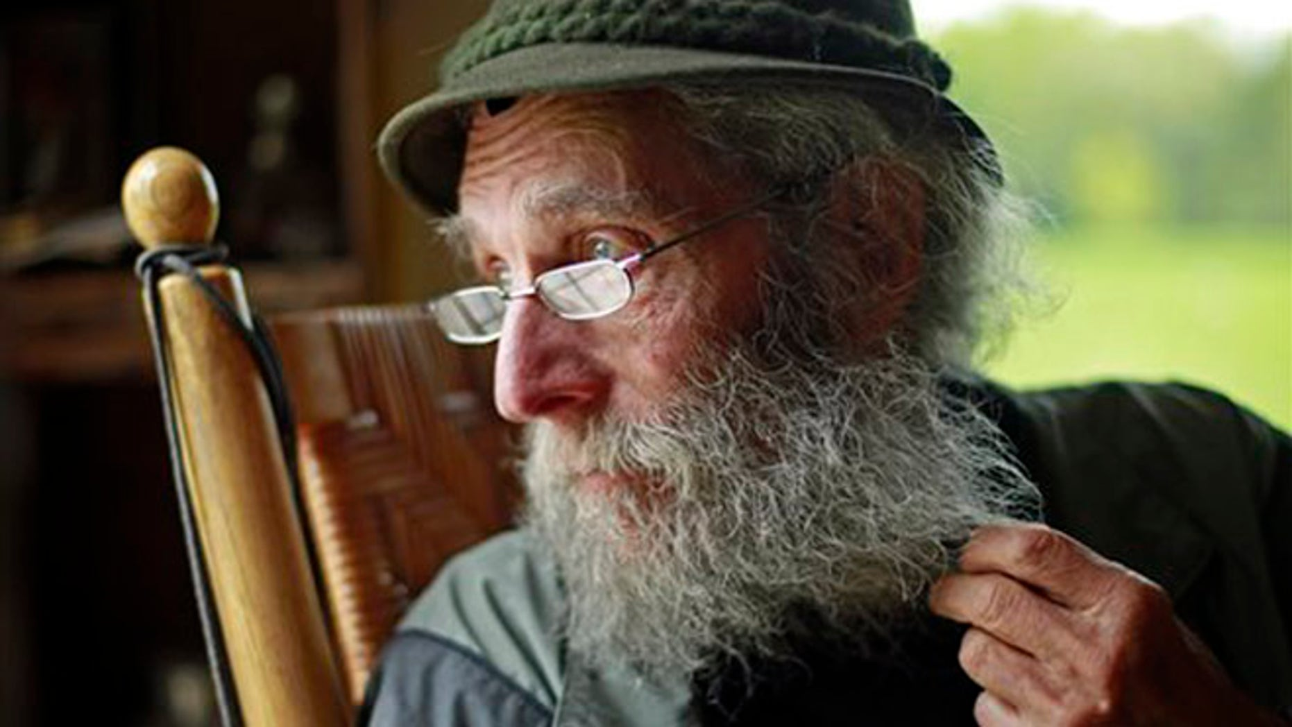 FILE- In May 23, 2014, file photo, Burt Shavitz pauses during an interview to watch a litter of fox kits play near his camp in Parkman, Maine. Shavitz, a former beekeeper, is the Burt behind Burt's Bees. A spokeswoman for Burts Bees said Shavtiz died Sunday, July 5, 2015, at his home in rural Maine. He was 80. (AP Photo/Robert F. Bukaty, File)