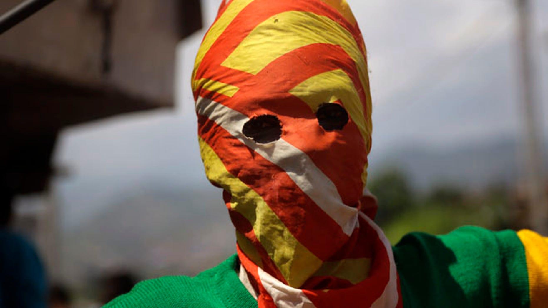 May 21, 2015: A masked Protester waits for  police during clashes in the Nyakabyga neighborhood of Bujumbura, Burundi. (AP)