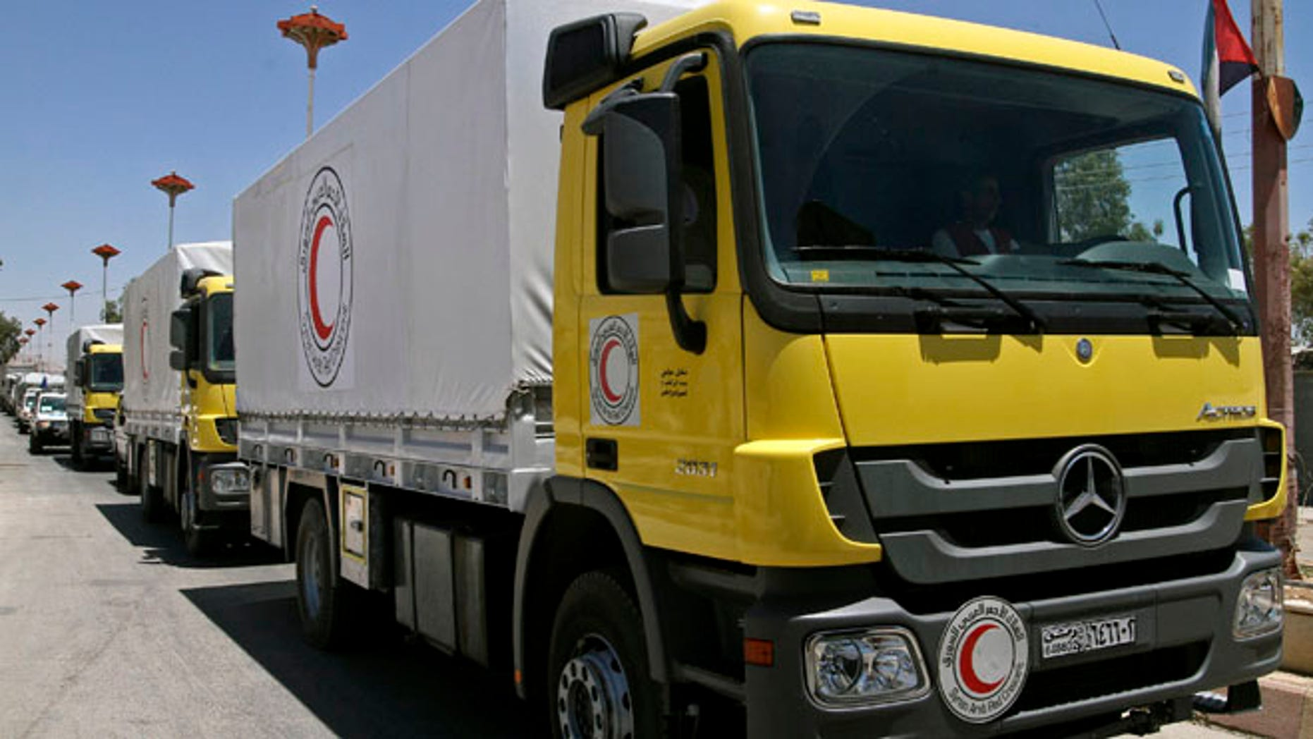 July 14, 2014: Syrian Red Crescent trucks loaded with food parcels under the supervision of the U.N., the Red Crescent and in coordination with the Syrian government, prepare to distribute aid to tens of thousands of besieged Syrians inside the rebel-held Damascus suburb of Moadamiyeh, Syria.