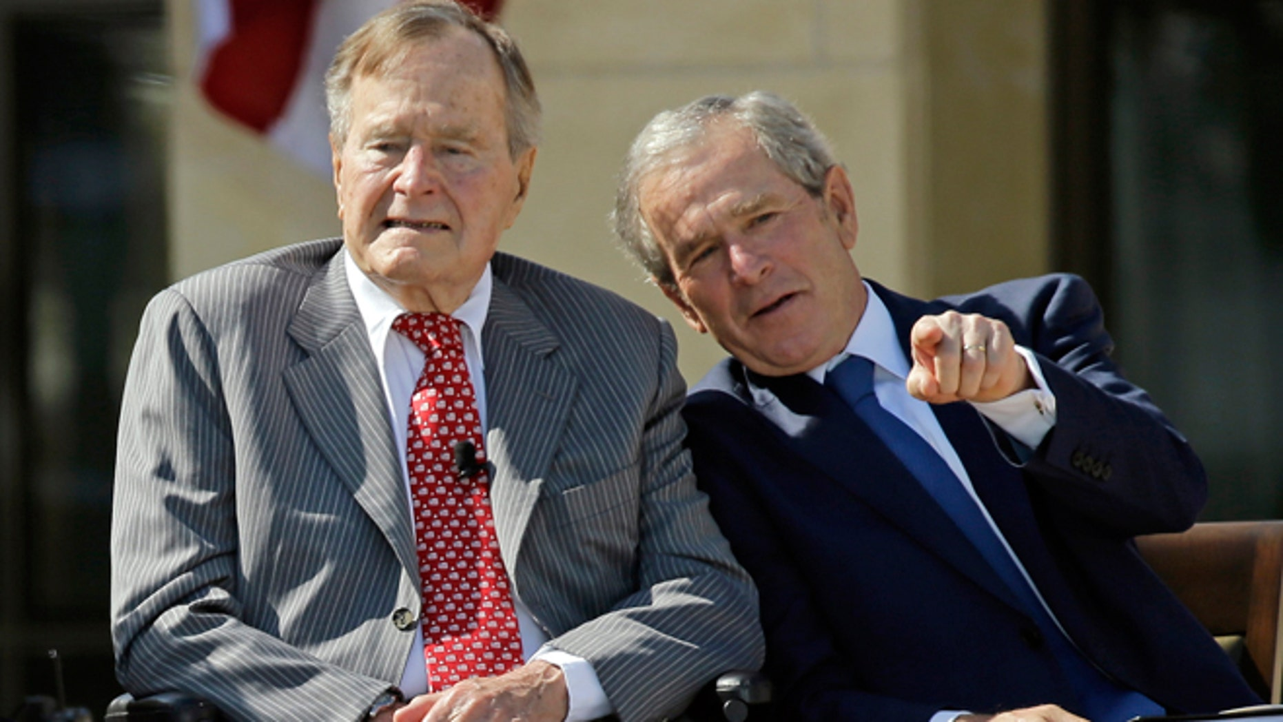 April 25, 2013: Former President George W. Bush talks with his father, former President George H. W. Bush, left, during the dedication of the George W. Bush Presidential Center in Dallas.