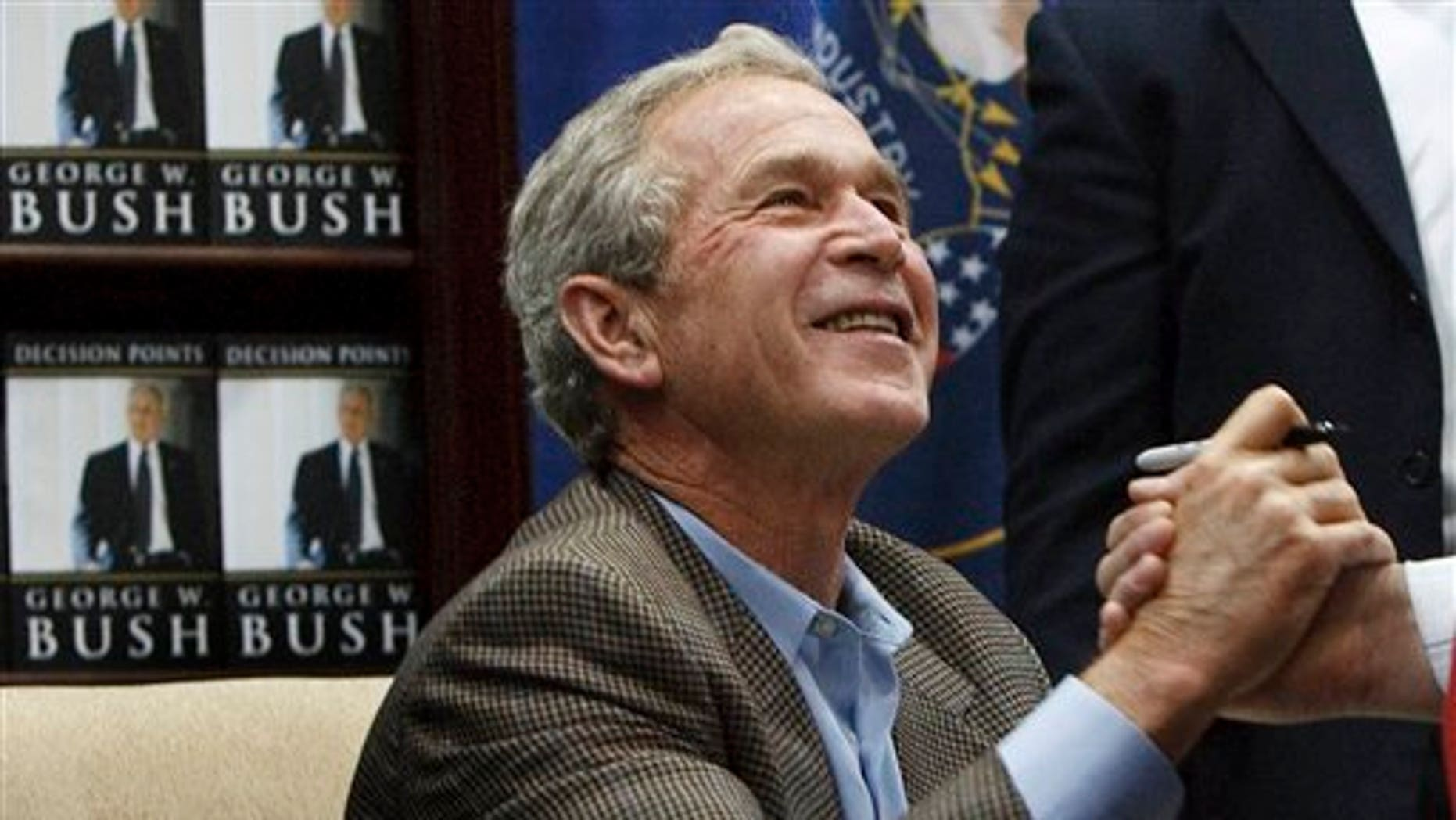 """Former President George W. Bush shakes hands with a man after autographing a copy of his memoir Friday, Nov. 19, 2010, in Sandy, Utah. More than 1,000 people were lined up waiting for an autographed copy of the former president's memoir, """"Decision Points."""""""