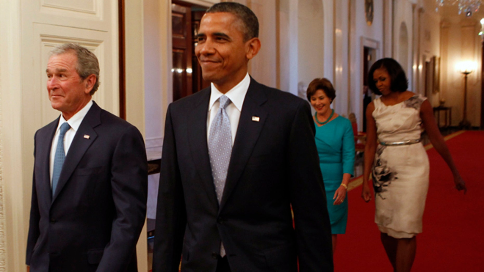 May 31, 2013: Former U.S. President George W. Bush (L) walks next to U.S. President Barack Obama (2nd L) while former first lady Laura Bush (2nd R) walks next to first lady Michelle Obama before the unveiling of the Bushs' official White House portraits in the East Room of the White House in Washington