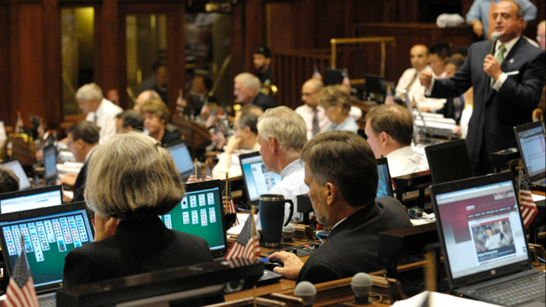 State legislators play solitaire and surf the internet on laptop computers while House Minority Leader Lawrence F. Cafero Jr. speaks prior to a vote on the state budget in 2009.