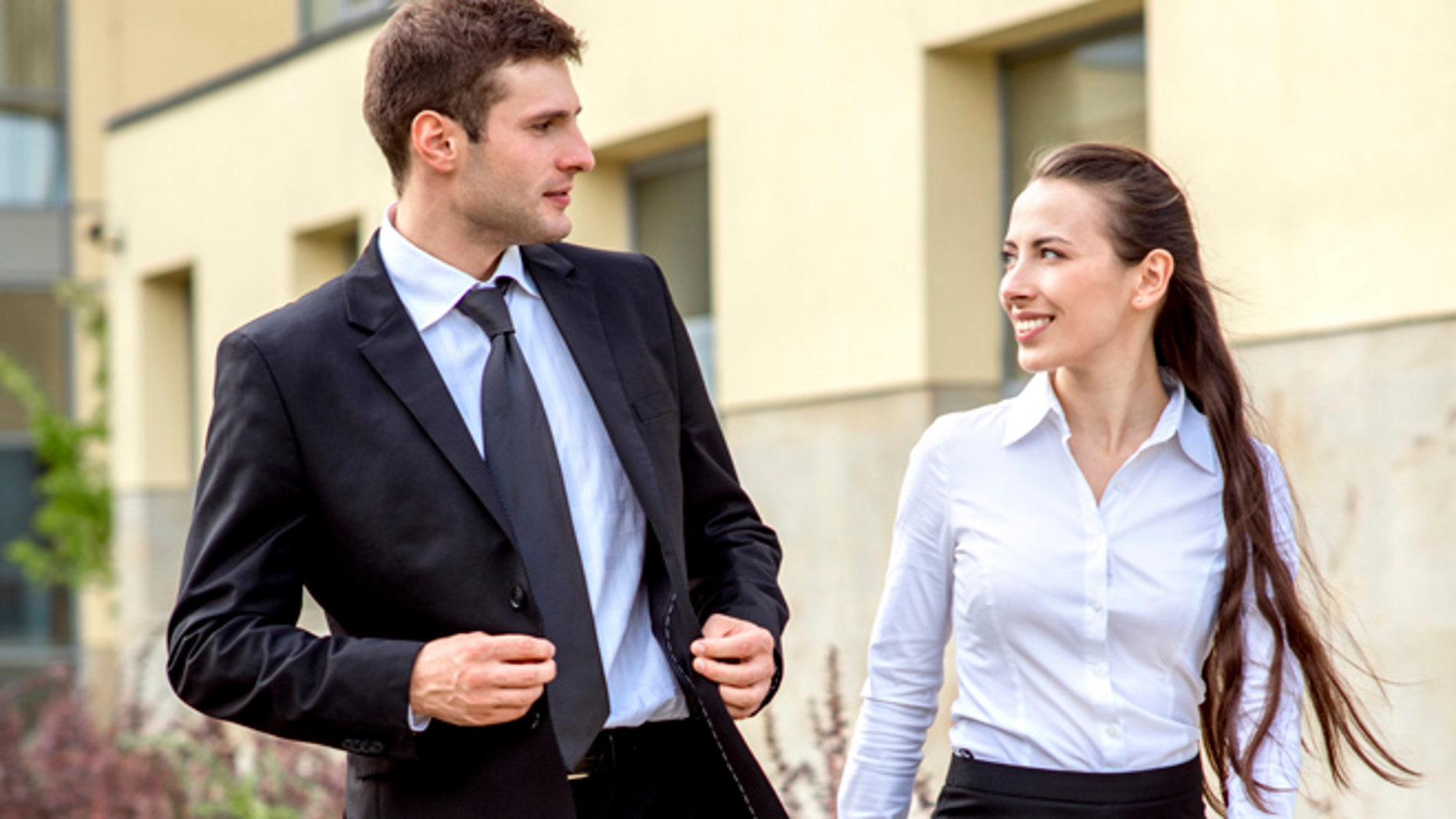 Young business couple walking outdoor near the office building