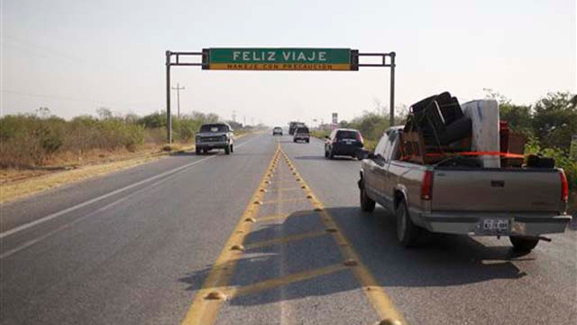 """Vehicles drive past a road sign that reads in Spanish """"Have a nice trip"""" at a highway between Ciudad Victoria and San Fernando, Tamaulipas State, Mexico, Wednesday, April 27, 2011. Security forces have unearthed six more bodies in Tamaulipas, a northeastern Mexican border state, where a drug gang is believed to be kidnapping passengers from buses and hiding their victims in secret graves, authorities said Tuesday. (AP Photo/Alexandre Meneghini)"""