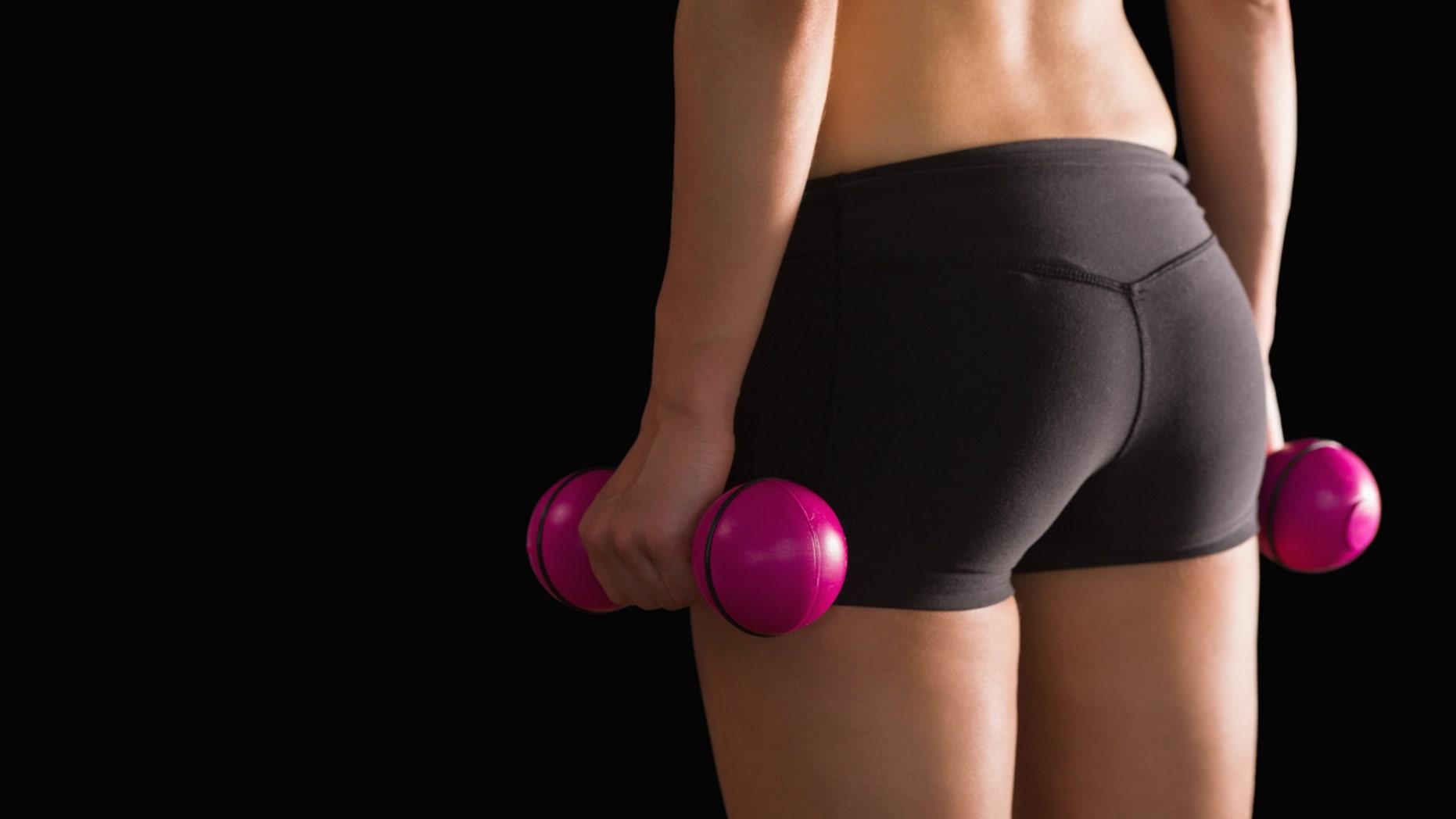 Rear view of slim woman wearing sportswear holding pink dumbbells on black background