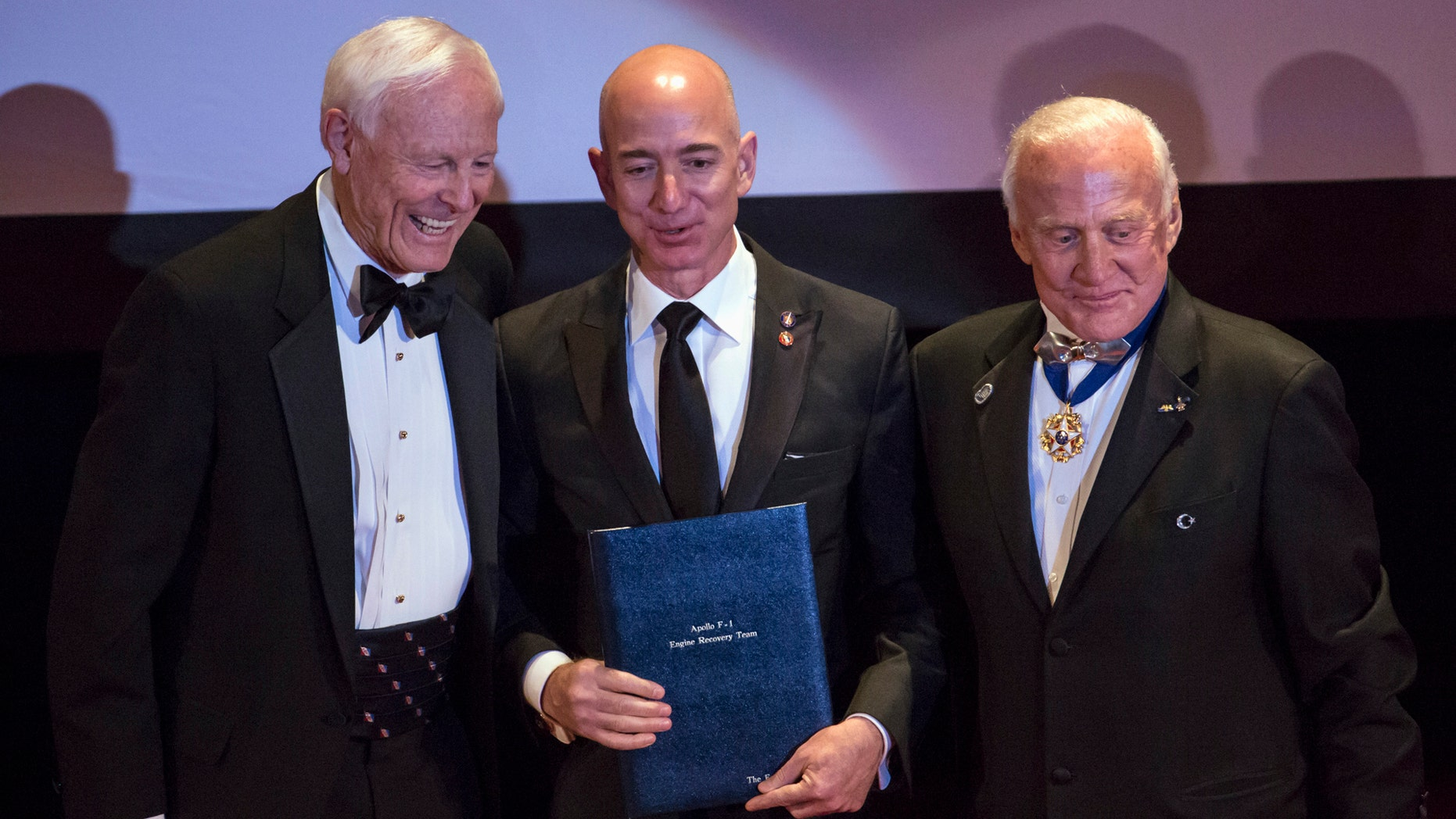 "File photo: Explorers Club President Alan Nichols (L) and Astronaut Edwin ""Buzz"" Aldrin (R) present the Citation of Merit to Amazon CEO and Chairman Jeff Bezos (C) and the Apollo F-1 Search and Recovery Team, at the 110th Explorers Club Annual Dinner at the Waldorf Astoria in New York March 15, 2014. (REUTERS/Andrew Kelly)"