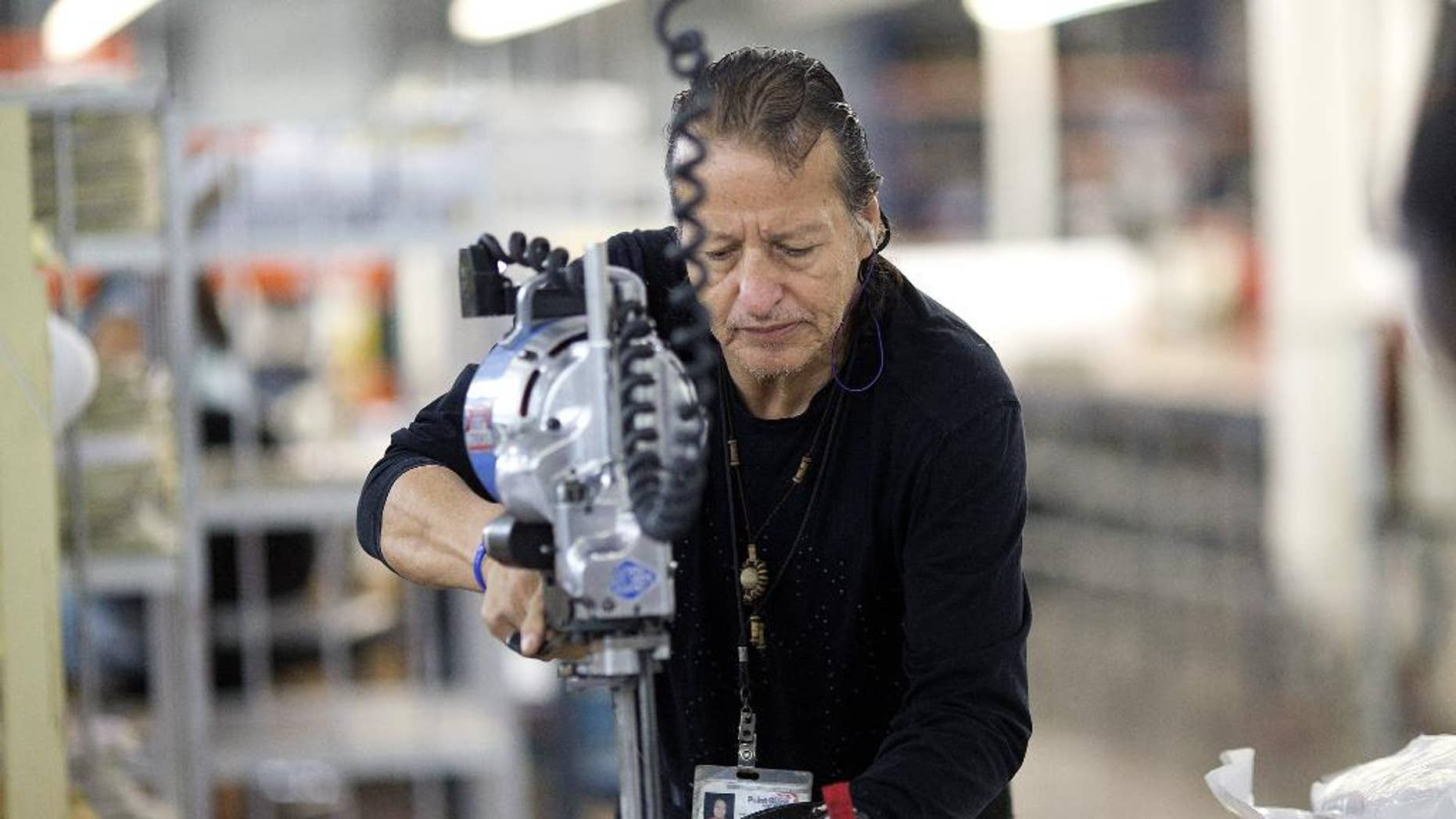 In this Sept. 19, 2014 photo, Adolfo Garzon cuts pieces for body armor at the Point Blank Body Armor factory in Pompano Beach, Fla. The Labor Department releases fourth-quarter productivity data on Thursday, March 5, 2015. (AP Photo/J Pat Carter)
