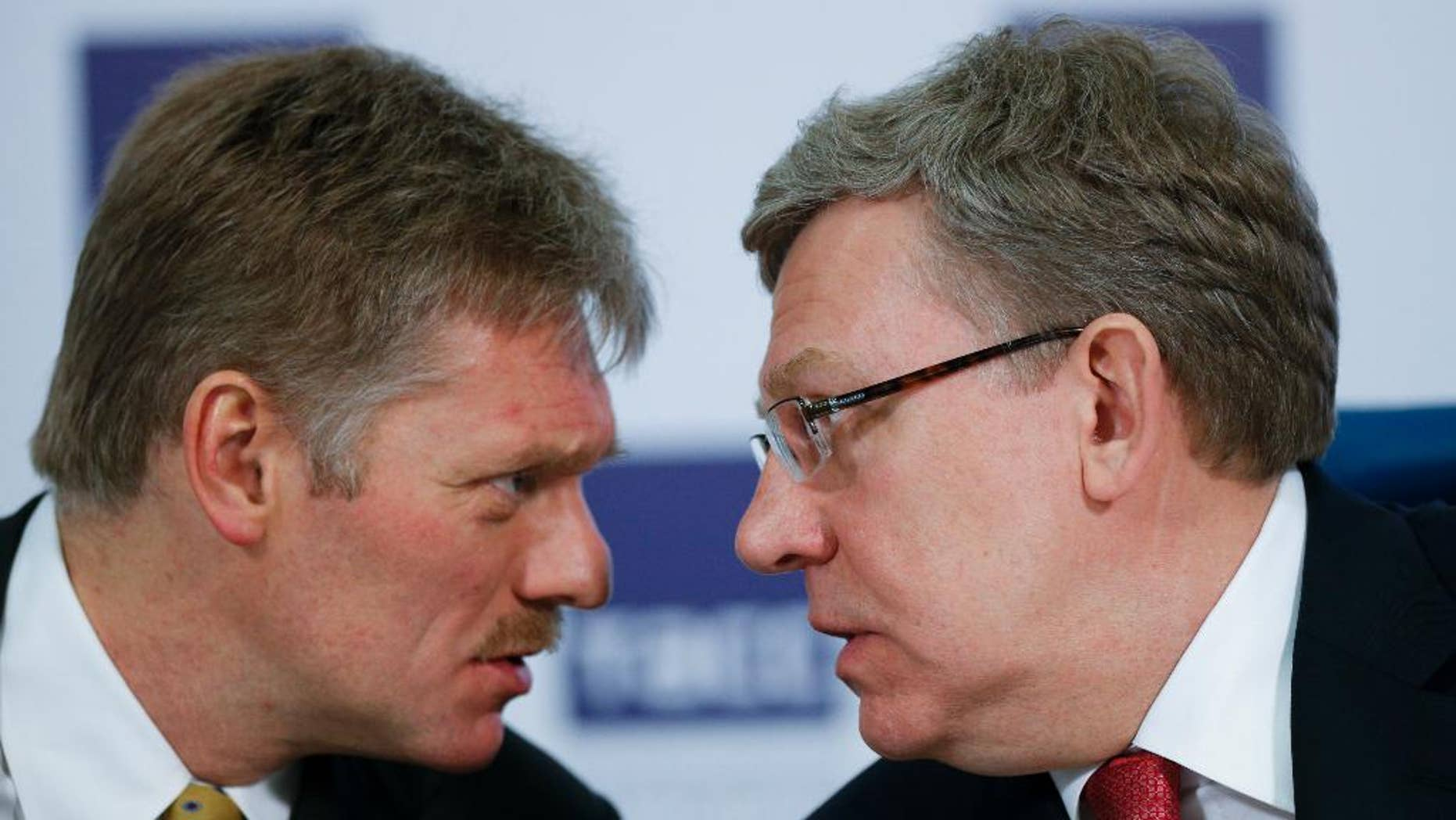 Russian President Vladimir Putin's press secretary Dmitry Peskov, left, speaks to Russia's former finance minister Alexei Kudrin at a round table to mark President Vladimir Putin's 15 years in office, some of the president's long-term allies questioned his political course and warned of economic fallout in Moscow, Russia, Tuesday, March 31, 2015. Alexei Kudrin, Russia's finance minister in 2000-2011 and a former deputy prime minister, said Tuesday that Putin's focus on foreign policy means that Russia won't return in the coming years to the economic growth that would suit a great power.  (AP Photo/Alexander Zemlianichenko)
