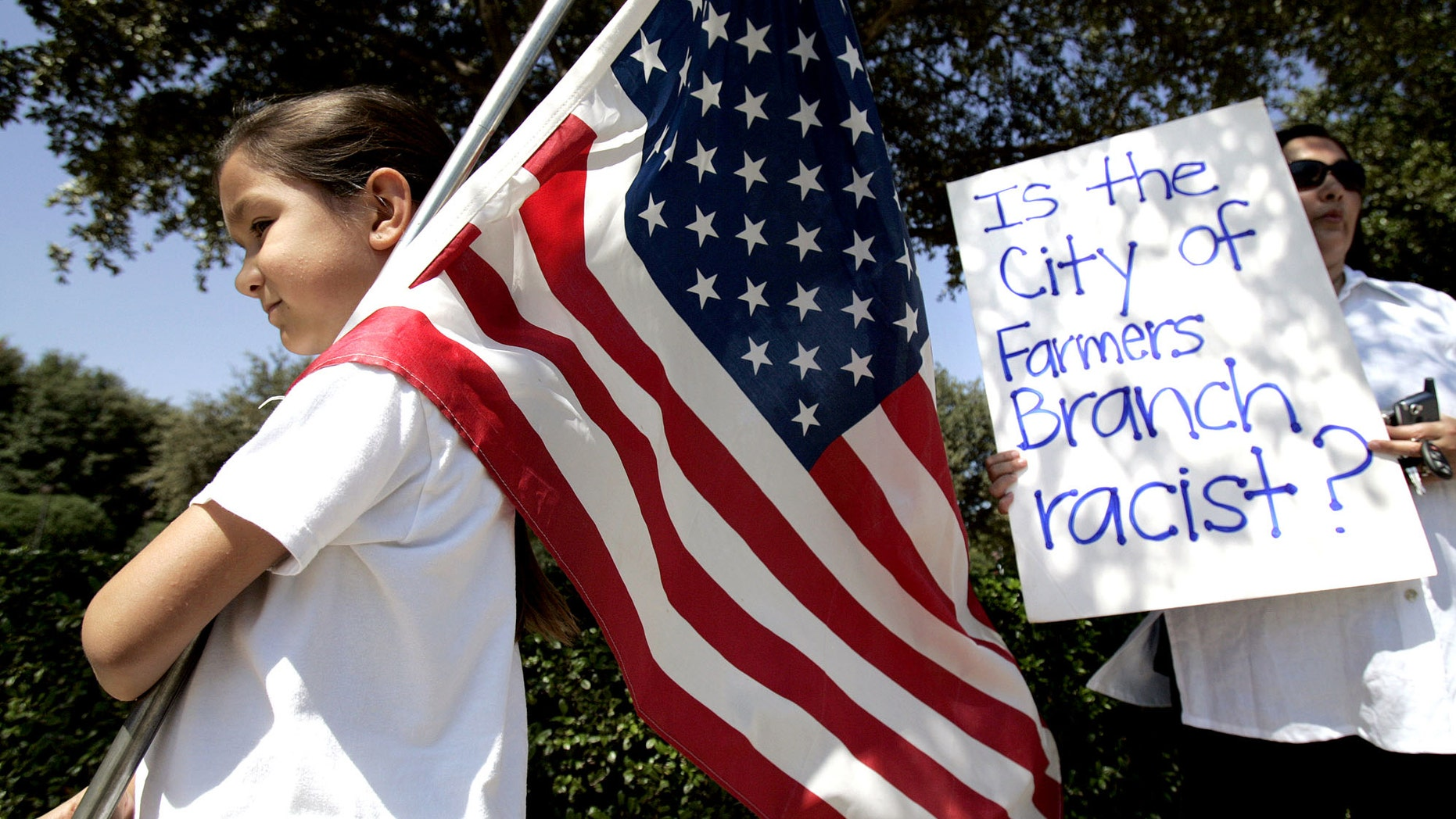 In this Aug. 26, 2006 file photo, Natalie Villafranca, 6, left, hold a flag as her mother, Elizabeth Villafranca, holds a sign in front of city hall in Farmers Branch, Texas, during an immigration law protest. (AP Photo/L.M. Otero, File)