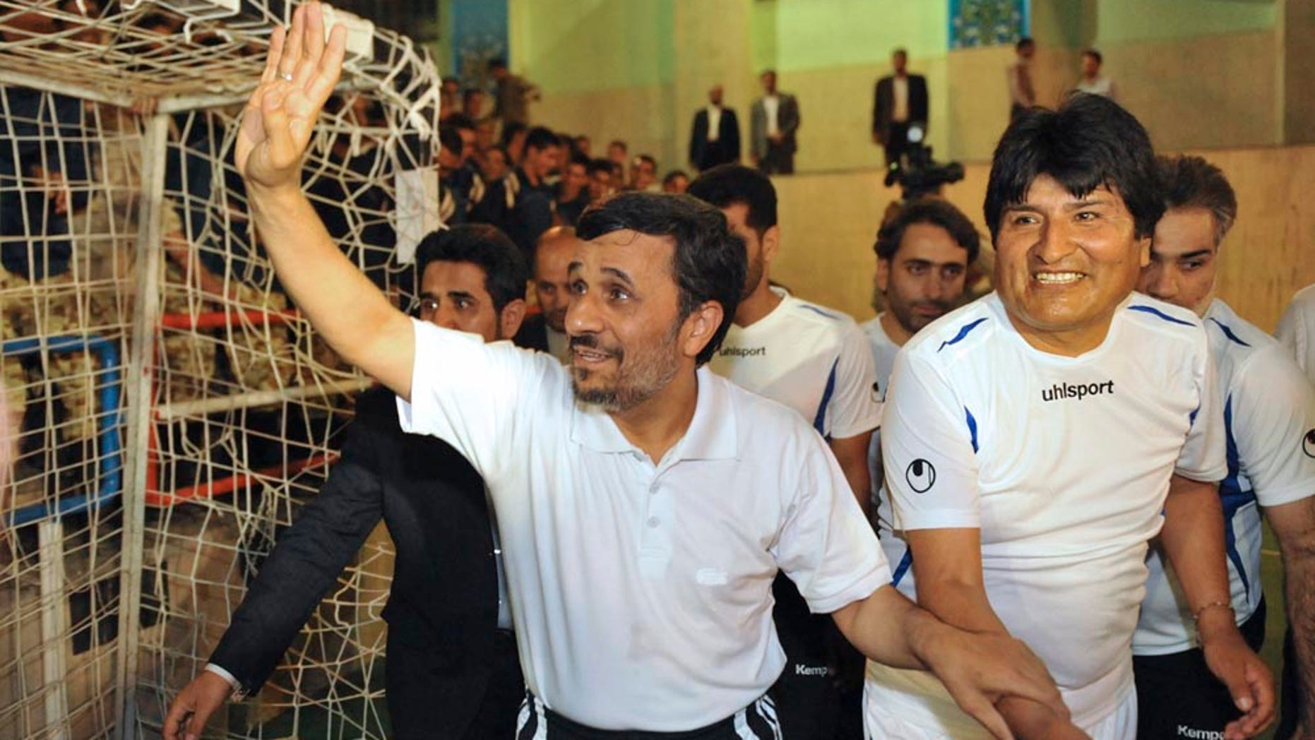 In this picture taken on Tuesday, Oct. 26, 2010, Iranian President Mahmoud Ahmadinejad, left, holds the hand of his Bolivian counterpart, Evo Morales, prior to a friendly Fursal, in Tehran, Iran. (AP Photo/ISNA, Amir Kholousi)