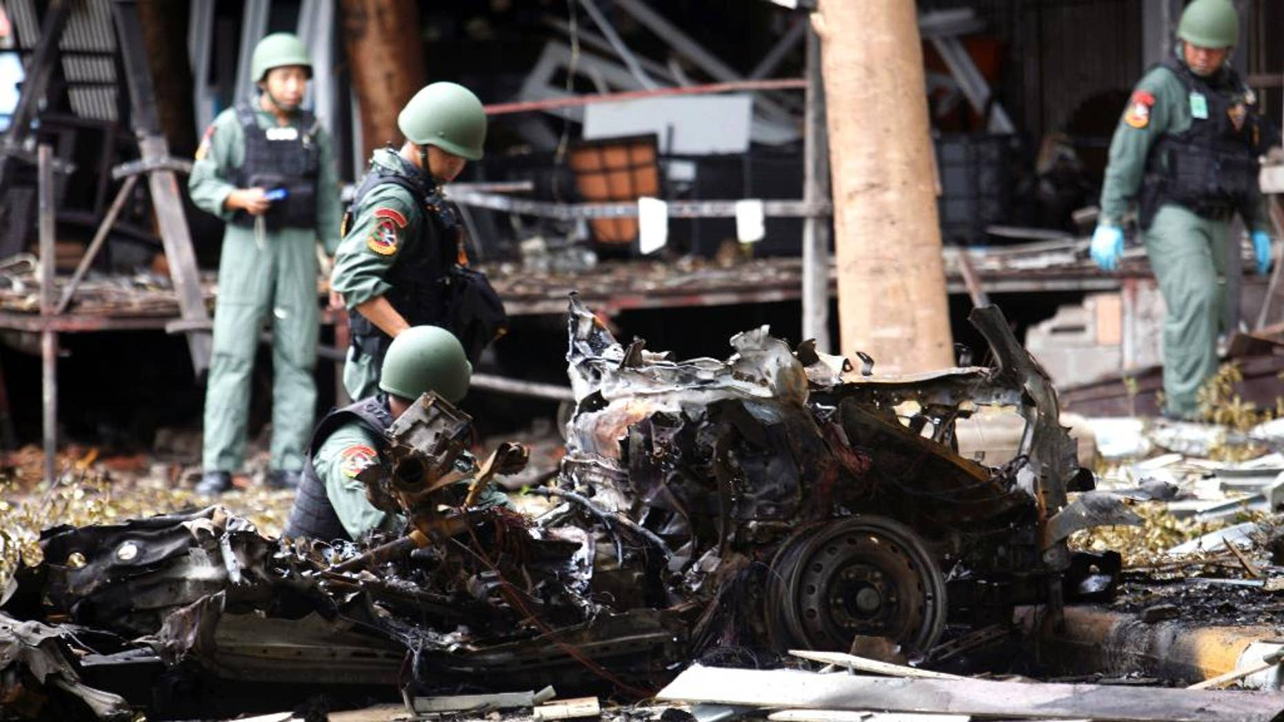 Thai bomb squad officers examine the wreckage of a car.