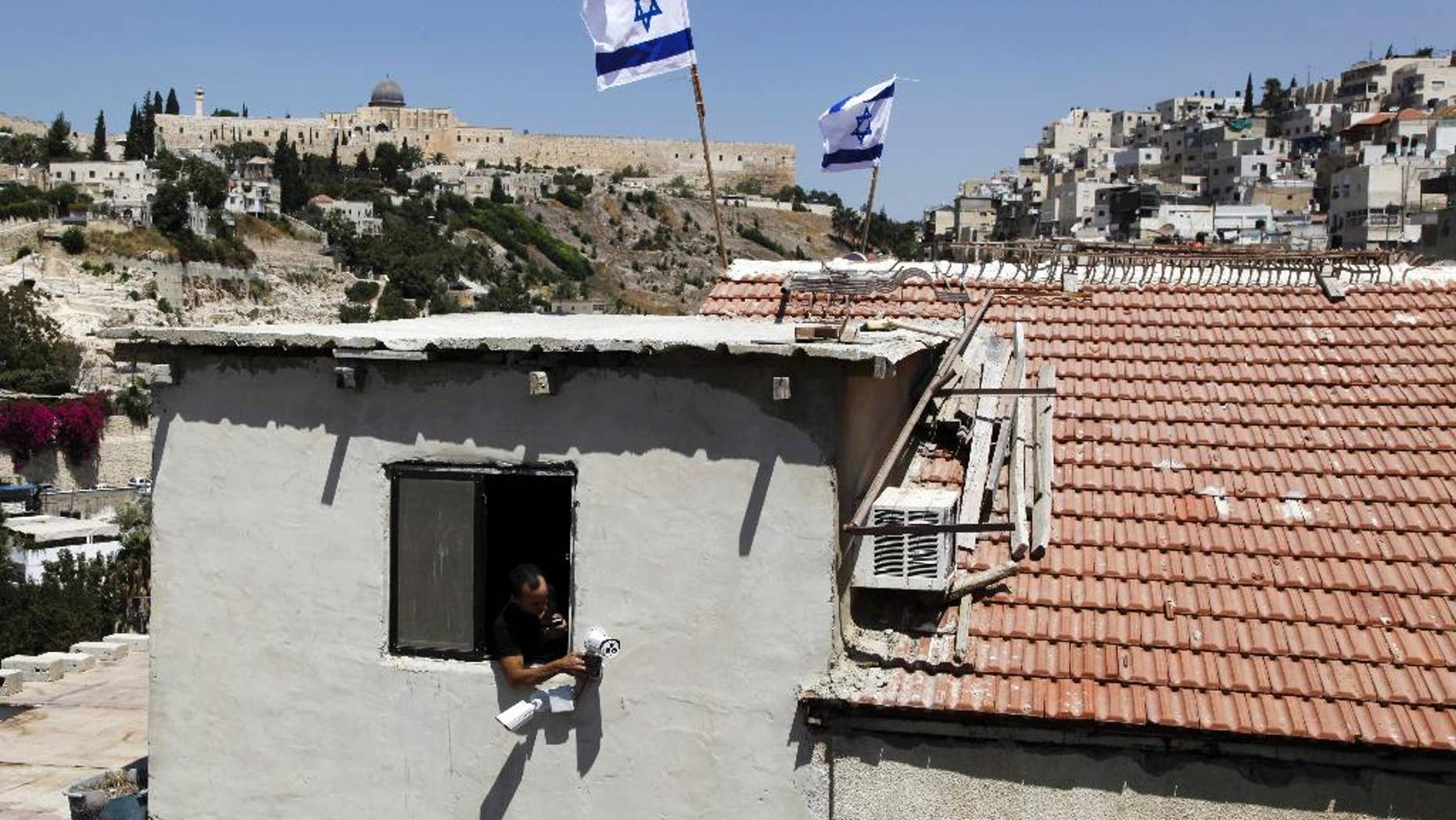 A man is seen from a window as Israeli flags fly on top of a house in Silwan neighborhood of east Jerusalem Thursday, Aug. 27, 2015. Ultra-nationalist Israelis have taken over the building in the heart of an Arab neighborhood in east Jerusalem, raising fears of fresh violence in the tense area. A small group of activists from the Ateret Cohanim settler organization moved into the building on Thursday. It was the latest in a wave of settler advances since nationalist Jews began buying up properties in Palestinian neighborhoods two decades ago. (AP Photo/Mahmoud Illean)