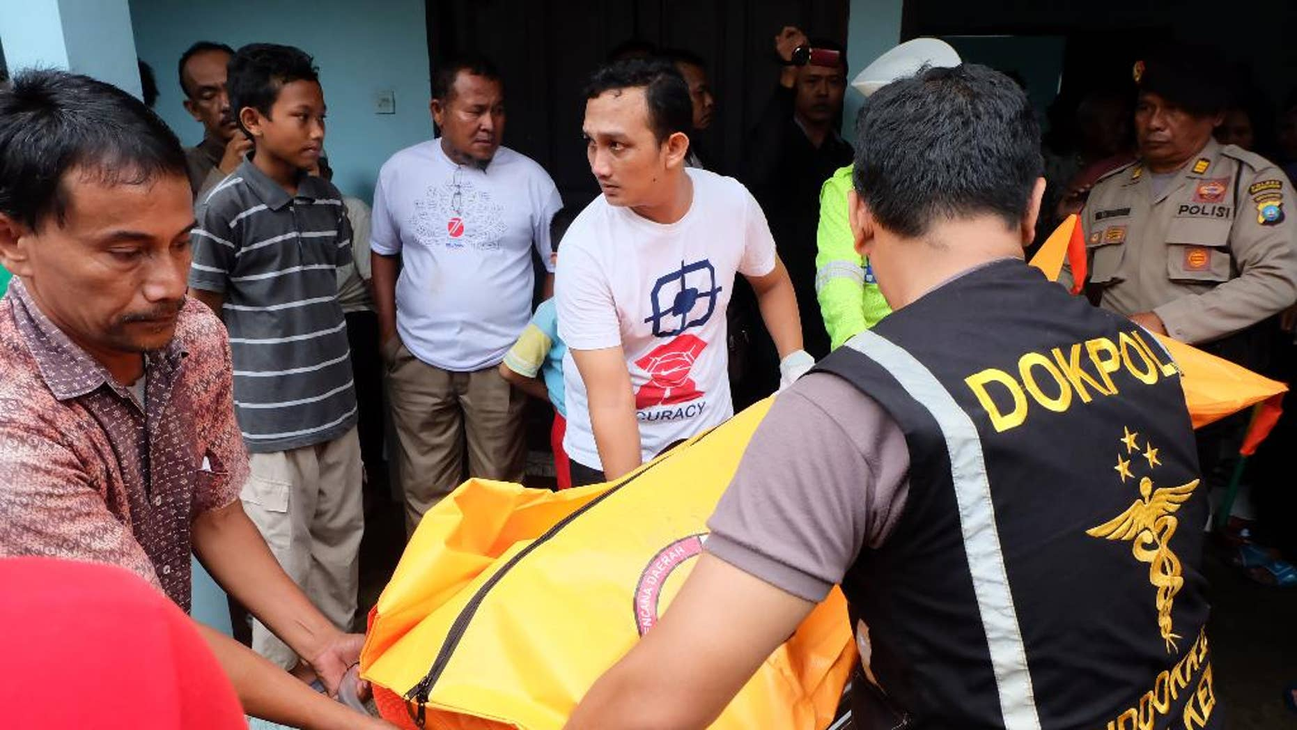 Indonesian police carry a body bag containing a victim of a capsized boat, at a hospital in Tanjungpinang, Bintan island, Indonesia, Sunday, Aug. 21, 2016. A number of people died and others were missing after a small wooden boat capsized in rough seas and sank Sunday off Indonesia's Bintan island, south of Singapore, Indonesian officials said.(AP Photo/Albert)