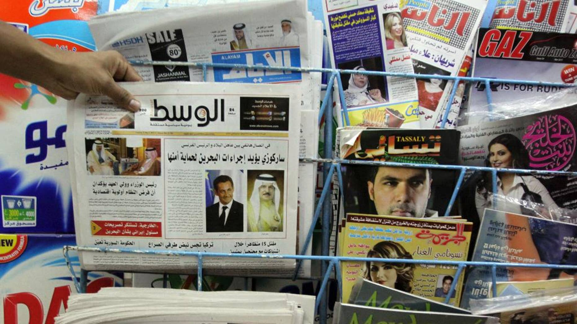File - In this Tuesday, April 5, 2011, file photo, a man picks up a copy of Al Wasat newspaper at a newsstand in Hamad Town, Bahrain. Bahraini authorities have ordered the independent newspaper to stop publishing online Monday and say a city hall was set ablaze during clashes between opposition protesters and police. The suspension of Al-Wasat's online operations followed a spike in anti-government protests led by the country's Shiite majority that began Saturday.  (AP Photo/Hasan Jamali, File)