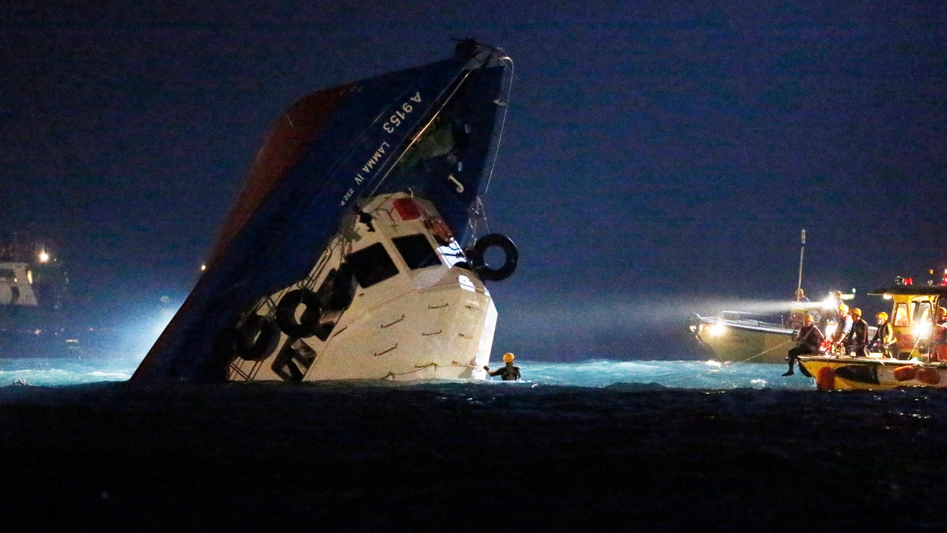 Oct. 2, 2012: Rescuers check on a half submerged boat after it collided Monday night near Lamma Island, off the southwestern coast of Hong Kong Island.