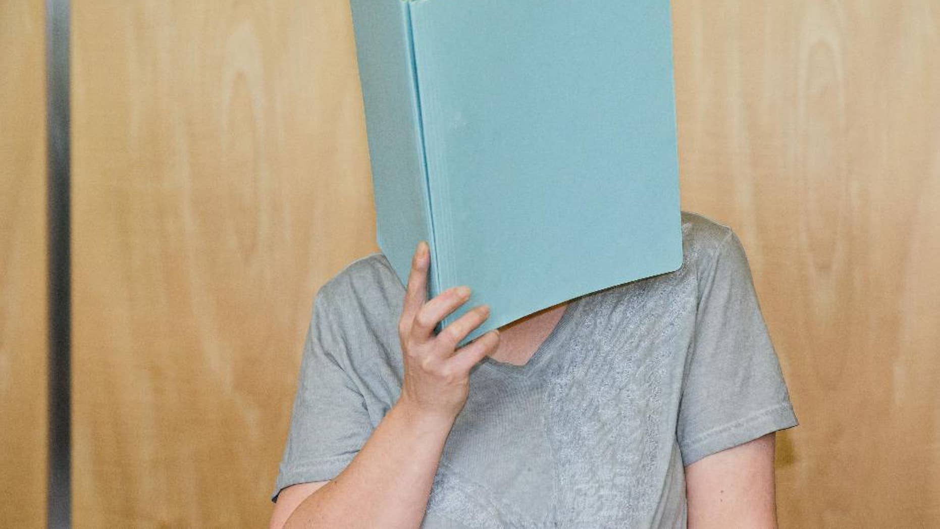 Defendant Andrea G., accused of murder, covering her face with a folder in the courtroom.