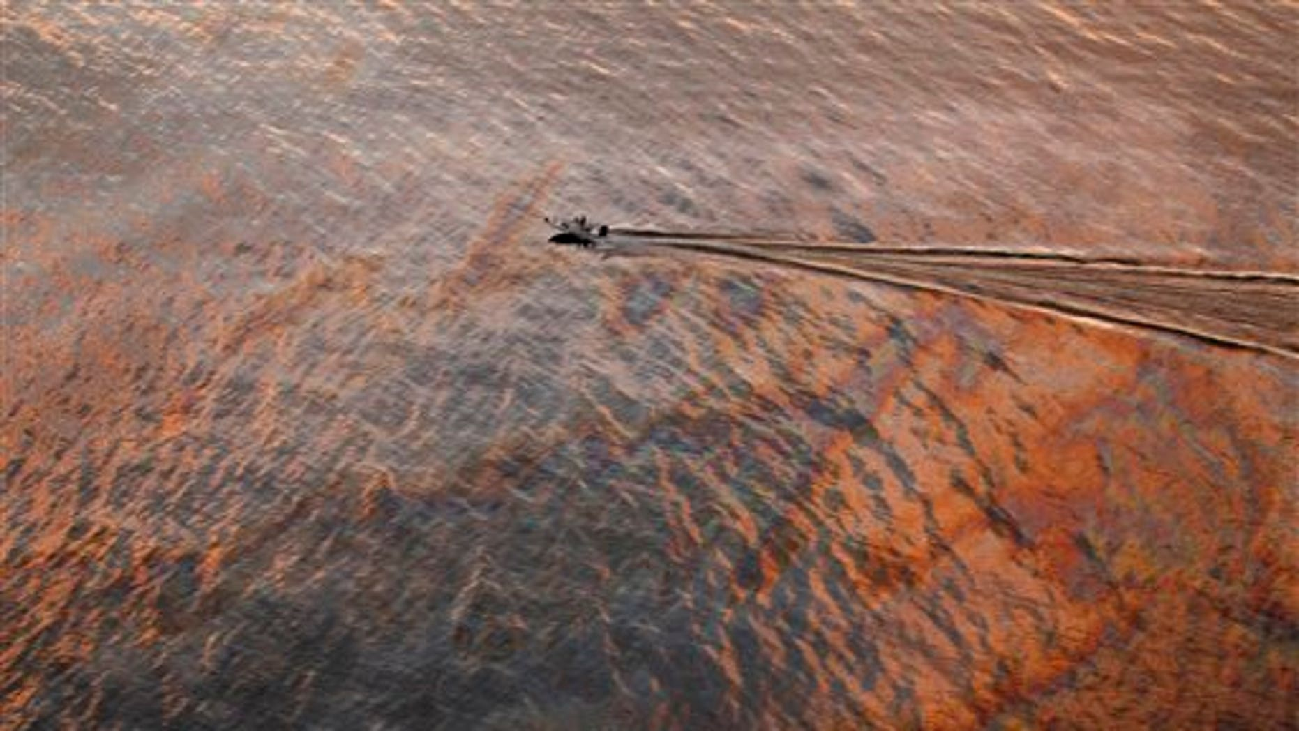 In this July 31, 2010 file photo, a boat motors through oil sheen from the Deepwater Horizon oil spill off East Grand Terre Island, where the Gulf of Mexico meets Barataria Bay, on the Louisiana coast, at sunset.  A year after one of the worst environmental disasters in U.S. history, drilling rigs once again are probing the depths of the Gulf of Mexico for oil. But the catastrophic prospect of a spill in oil's next frontier -- the icy waters off Alaska's north coast -- has experts far more concerned.  (AP/File)