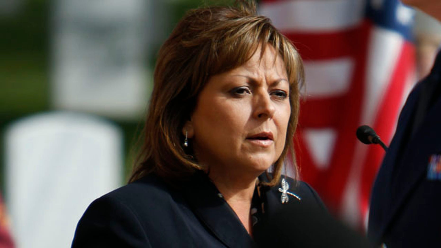In this Tuesday Nov. 1, 2011 photo, Gov. Susana Martinez speaks during the memorial service for 10 veterans at the Santa Fe National Cemetery as part of the Missing in America Project. According to the web site, the purpose of the MIA Project is to locate, identify and inter the unclaimed cremated remains of American veterans through the joint efforts of private, state and federal organizations. The services were in memory of retired Col. John Garnett Coughlin, retired Col. Jackson Evert Shirley, retired Lt. Edward Grimm Lucius, Chief Petty Officer Donald Claire Smith, Petty Officer 2nd Class Milton Vincin Burroughs, Technician Third Class Gerald Edwin Huber, Technician Third Class Richard Landrum Thomas, Airman 1st Class Charles Thomas Stewart, Pvt. John L. Craft, and Pvt. Hanry D. Nichols. (AP Photo/The Santa Fe New Mexican, Luis Sanchez Saturno)