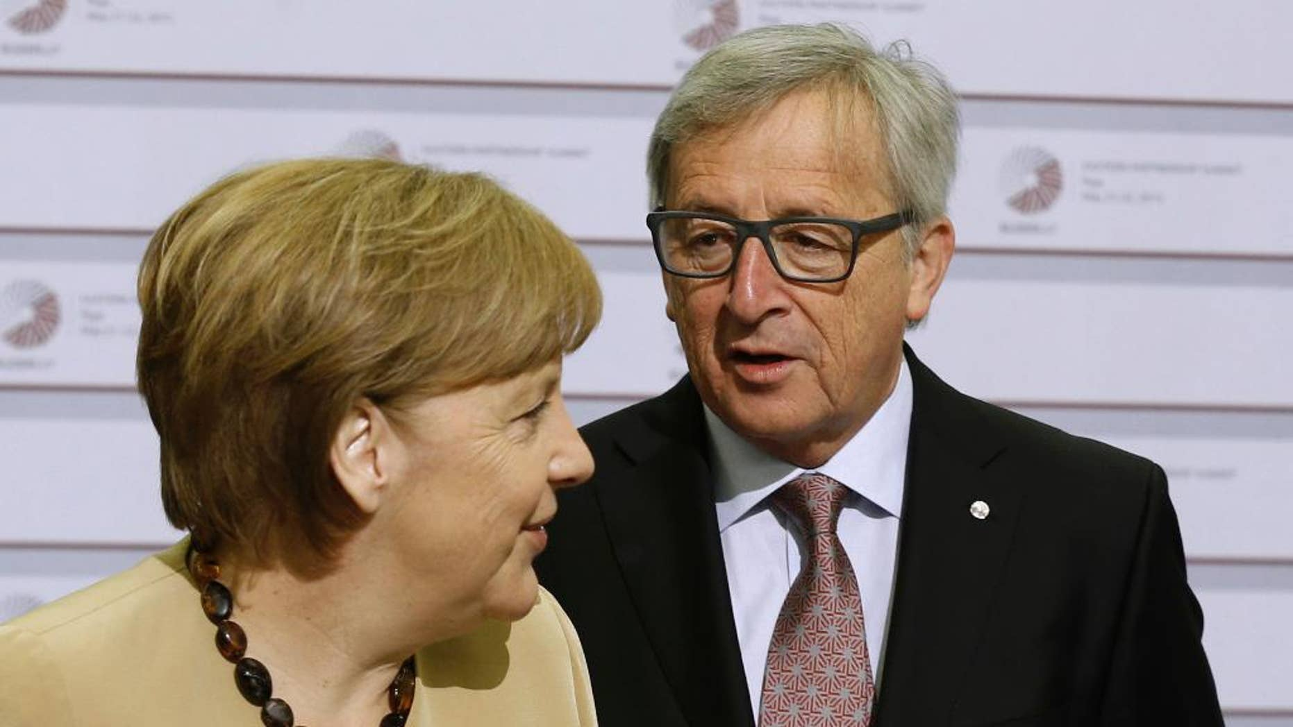 European Commission President Jean-Claude Juncker, right, greets German Chancellor Angela Merkel during arrivals for the Eastern Partnership summit in Riga, Latvia on Friday, May 22, 2015. EU leaders gathered for a second day of meetings with six post-communist nations to discuss various issues, including enlargement, the economy and Ukraine. (AP Photo/Mindaugas Kulbis)
