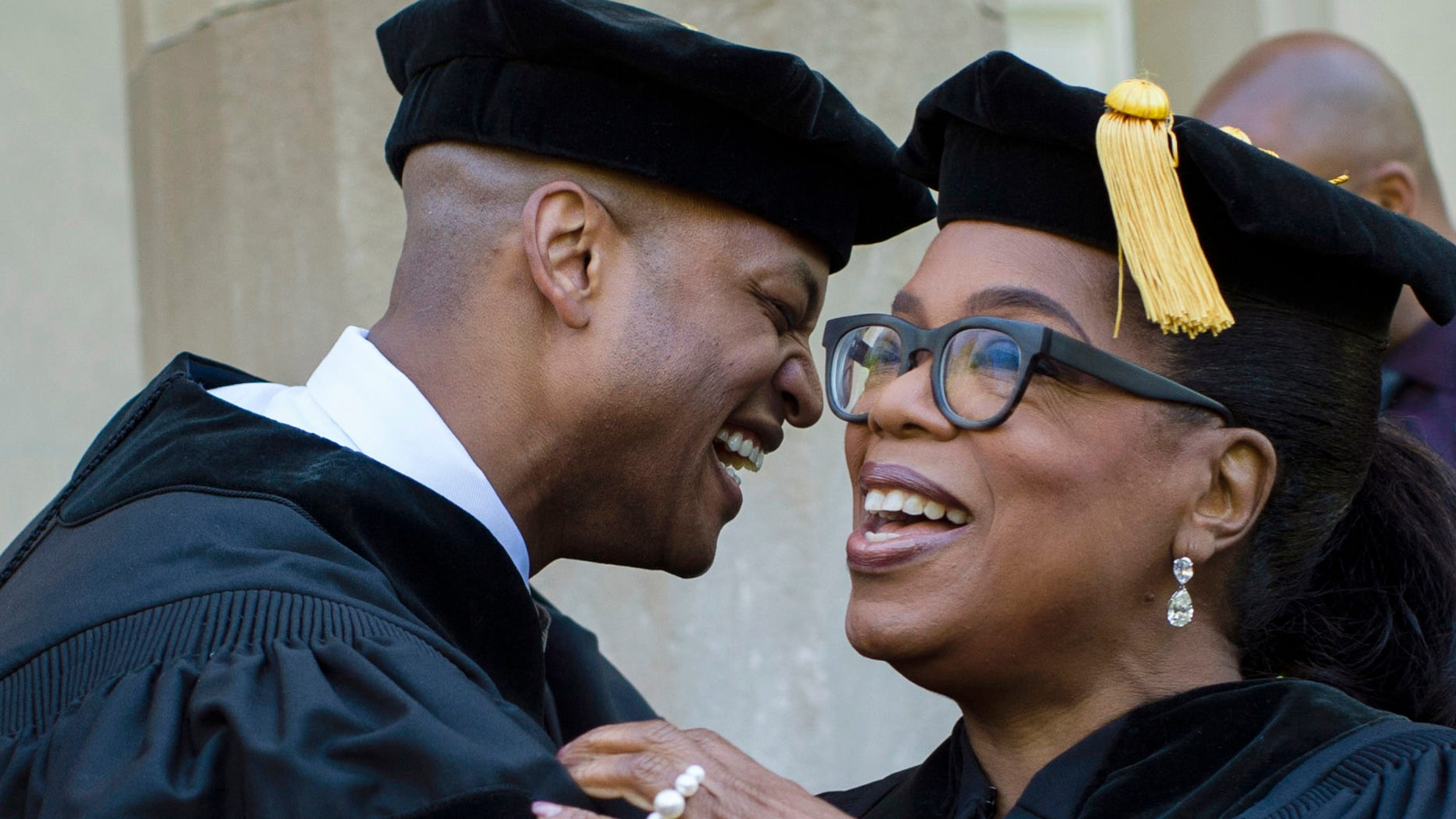 In this photo provided by Skidmore College, author Wes Moore embraces Oprah Winfrey at Skidmore College's 106th Commencement, Saturday, May 20, 2017 at the Saratoga Performing Arts Center, in Saratoga Springs, N.Y. The author, actress and former talk show host spoke at the graduation. (Erin Covey/Skidmore College via AP)