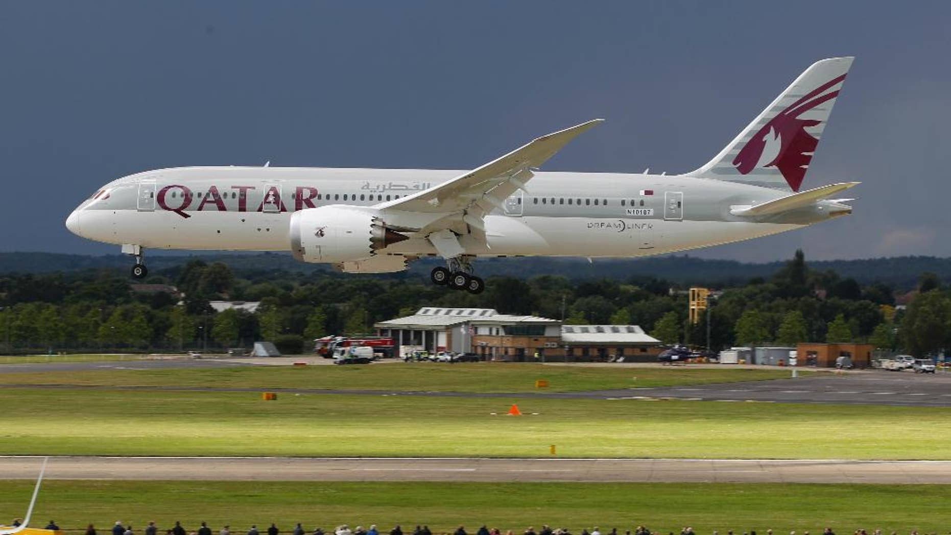 FILE- in this file photo dated Wednesday, July 11, 2012, onlookers watch as a Qatar Airways Boeing 787 Dreamliner lands during an aerial display at the Farnborough International Airshow, in Farnborough, England.  The state-owned Commercial Aircraft Corp. of China, known as Comac, announced plans this week at Farnborough airshow 2016, for a wide-body aircraft to be built with state-owned Russian maker United Aircraft Corporation, striking at the heart of the market leaders Airbus and Boeing. (AP Photo/Lefteris Pitarakis, FILE)