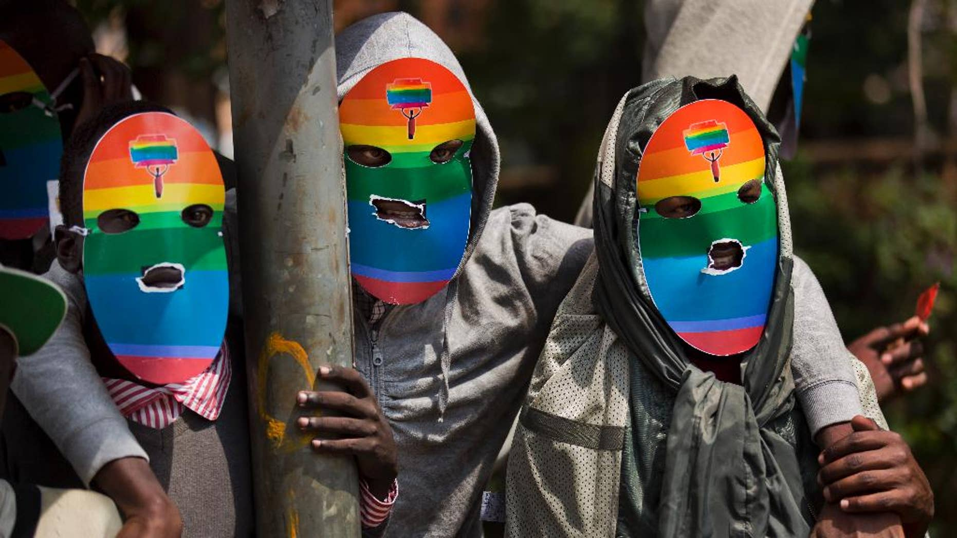 """FILE - In this Monday, Feb. 10, 2014 file photo, Kenyan gays and lesbians and others supporting their cause wear masks to preserve their anonymity as they stage a rare protest. Human Rights Watch is urging an end to """"forced anal examinations"""" with a report documenting them in eight countries, mostly in Africa, saying the practice is based on flawed ideas about supposedly proving homosexual conduct. (AP Photo/Ben Curtis, File)"""