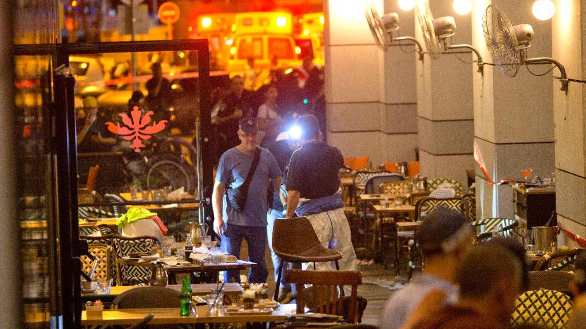 Israeli police officers examine the scene of a shooting attack in Tel Aviv, Israel, Wednesday, June 8, 2016. Two Palestinian gunmen opened fire in central Tel Aviv Wednesday night, killing three people and wounding at least five others, Israel police said. (AP Photo/Sebastian Scheiner)