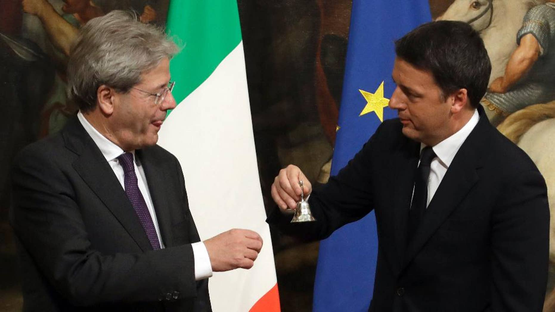 Italian outgoing Premier Matteo Renzi, right, hands over the cabinet minister bell to new Premier Paolo Gentiloni during the handover ceremony at Chigi Palace Premier's office, in Rome, Monday, Dec. 12, 2016. Paolo Gentiloni, a Democrat serving as foreign minister, formed Italy's new government Monday, keeping several key ministers from the coalition of Matteo Renzi, who resigned last week. (AP Photo/Gregorio Borgia)