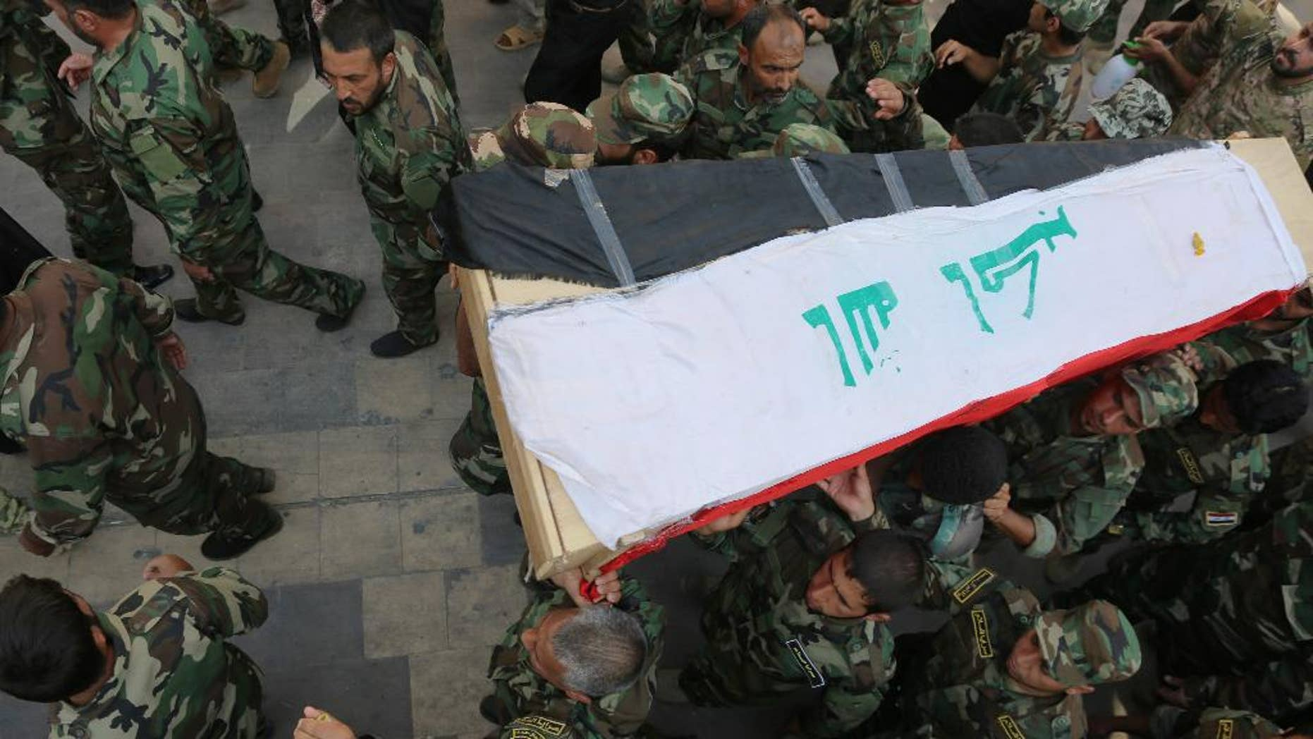 Shiite militiamen carry the flag-draped coffin of their colleague who was killed during clashes with Islamic militants in the town of Amirli, Iraq, on Wednesday, during his funeral procession in the Shiite holy city of Najaf, 100 miles (160 kilometers) south of Baghdad, Iraq, Thursday, Sept. 4, 2014. The Islamic State group has carved out a self-styled caliphate in the large area straddling the Iraqi-Syrian border that it now controls. In early August, the United States launched air strikes on the militant group in Iraq, in an effort to help Iraqi forces fight back against the growing militant threat. (AP Photo/Jaber al-Helo)