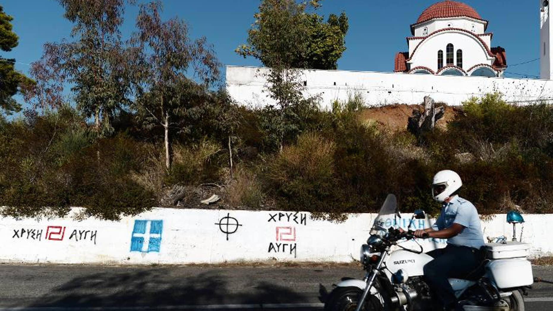 A policeman rides his motorcycle in front of Golden Dawn and nationalist graffiti in southern Greece, on September 29, 2013. Greek police swooped on the neo-Nazi Golden Dawn party, arresting its leadership and hunting for dozens of members across the country in a crackdown sparked by the murder of a leftist musician. AFP PHOTO / ARIS MESSINIS