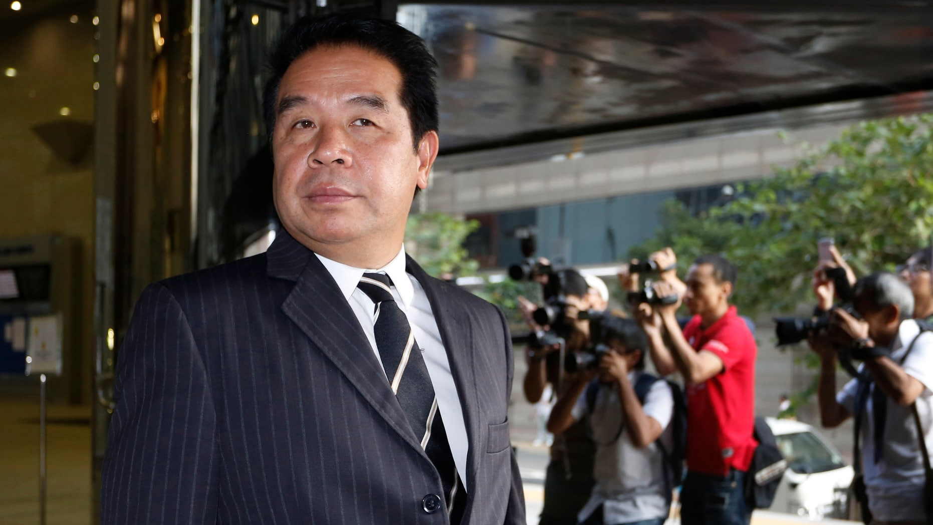 FILE - In this Tuesday, Oct. 15, 2013 file photo, Birmingham City F.C. owner Carson Yeung leaves Hong Kong District Court in Hong Kong after giving testimony in his money laundering trial. Yeung said he's a celebrity hairdresser, property developer, casino high-roller and millionaire stock investor. Hong Kong prosecutors said the owner of the football club is a money launderer who grossly inflated his income. (AP Photo/Vincent Yu, File)