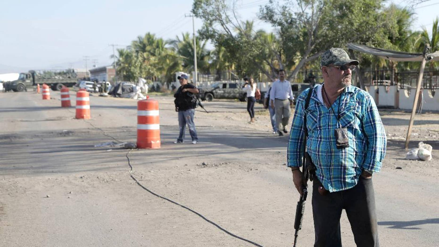 "FILE - In this Dec. 17, 2014, file photo, the leader of a local self-defense group, Hipolito Mora, right, stands armed at the entrance of the town of La Ruana, a day after a clash between two rival ""self-defense"" groups outside of the town, in the state of Guerrero, Mexico. Federal security commissioner in Michoacan, Alfredo Castillo said Tuesday Dec. 30, 2014, that two leaders and nearly three dozen members of rural self-defense forces in the western state of Michoacan who were involved in Dec. 17 clash, have turned themselves in to authorities. (AP Photo/Gustavo Aguado, File)"
