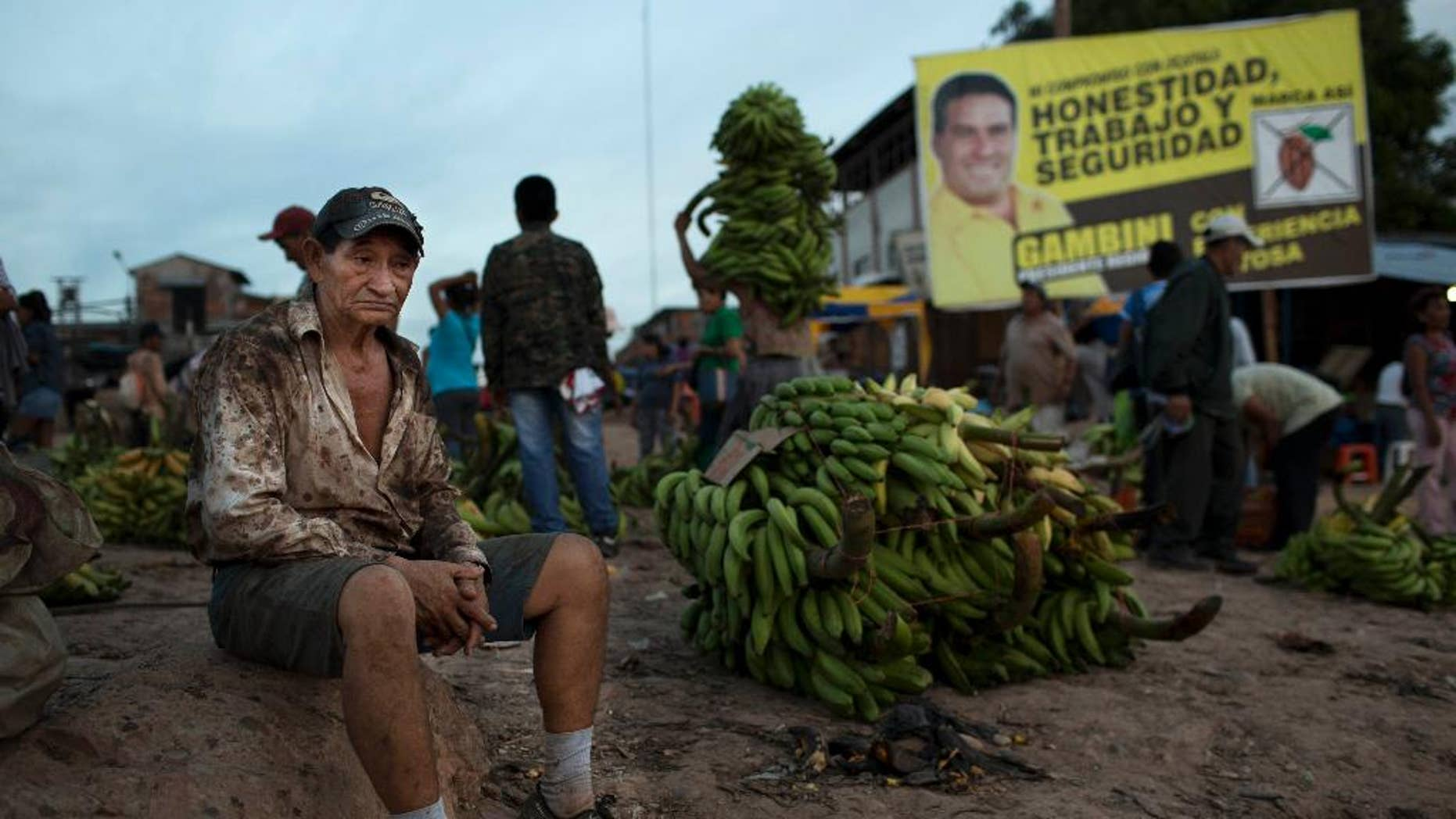 "CHANGES OFFENSE TO MONEY LAUNDERING - In this Sept. 26, 2014 photo, a worker rests near a campaign banner that reads in Spanish; ""Honesty, Jobs and Security,"" promoting gubernatorial candidate Manuel Gambini, in the port of Pucallpa, Peru. Gambini only entered the governor's race in adjacent Ucayali state after a money laundering charge of the incumbent made national headlines, sidelining him. As two-term mayor of Irazola, a poor farming district where the Andes meet the Amazon, Gambini enriched himself, relatives and associates ""closely tied to drug trafficking,"" according to an eight-page order for a money laundering probe issued Aug. 29 and obtained by The Associated Press. (AP Photo/Rodrigo Abd)"
