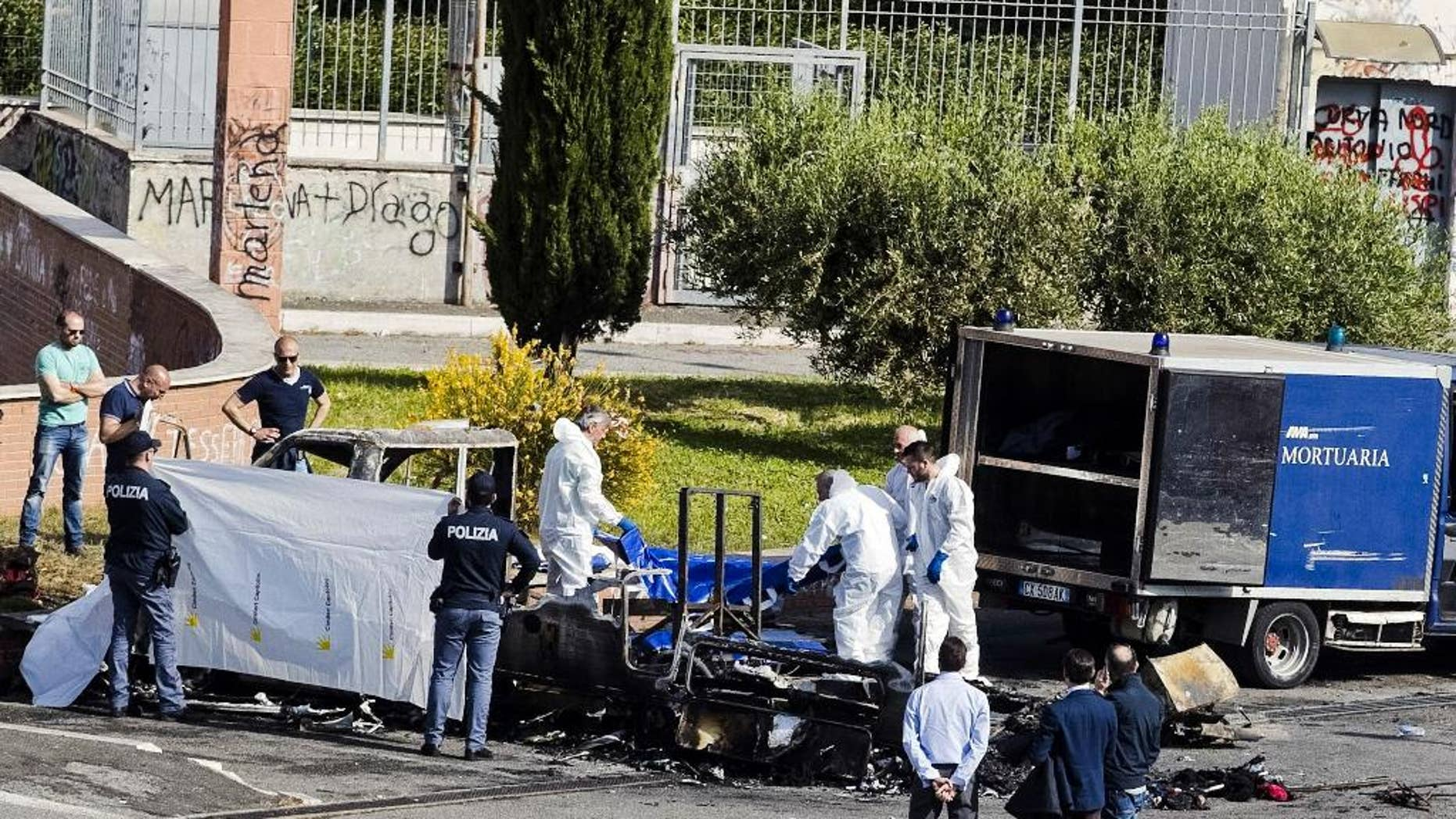Forensic police recover a body from the a camper where three sister died, in Rome, Wednesday, May 10, 2017, when it burst into flames as they slept, in what news reports said might have been an intentional attack aimed at Roma, also known as Gypsies. Prosecutors have opened an arson investigation after surviving family members reported having received threats from local residents in recent days and another camper was torched last week nearby. The sisters aged 4, 8 and 20, were Roma and other family members who were in the camper at the time managed to escape. (Massimo Percossi/ANSA via AP)