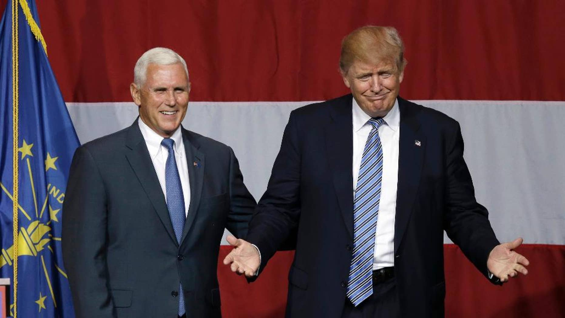 FILE - In this July 12, 2016 file photo, Indiana Gov. Mike Pence joins Republican presidential candidate Donald Trump at a rally in Westfield, Ind. Over the past two decades, Trump has disagreed with his vice-presidential pick on plenty of political issues, including immigration policy, entitlement programs and trade. On social issues above all, Trump and Pence arrive at the 2016 general election from very different paths.  (AP Photo/Michael Conroy, File)