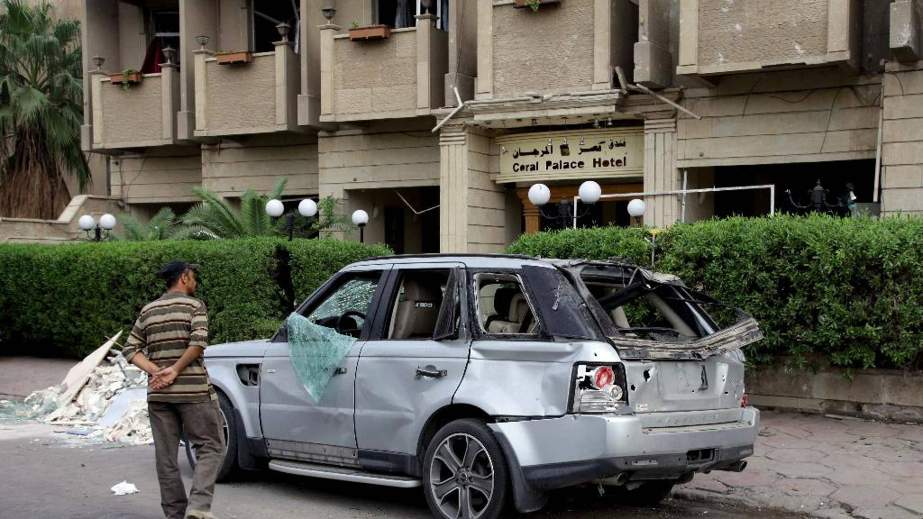 An Iraqi man inspects a damaged vehicle in the aftermath of a car bomb explosion in Baghdad, Iraq, Tuesday, Oct. 28, 2014. On Monday night, a car bomb blast near a line of shops and restaurants in downtown Baghdad killed more than a dozen and wounded tens, police said. (AP Photo/Khalid Mohammed)
