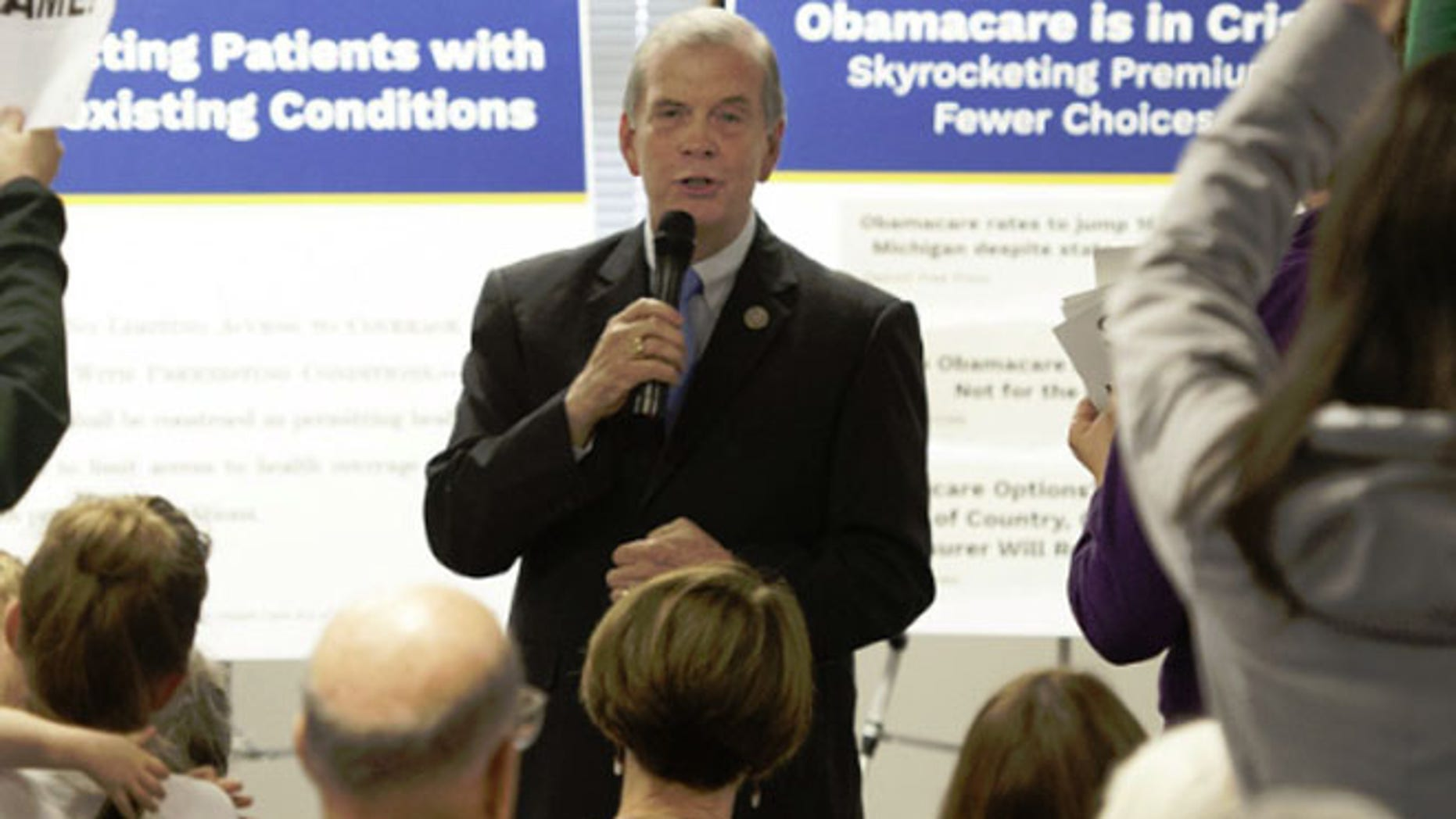 Rep. Tim Walberg speaks as people stand in protest during a town hall meeting in Jackson, Mich.