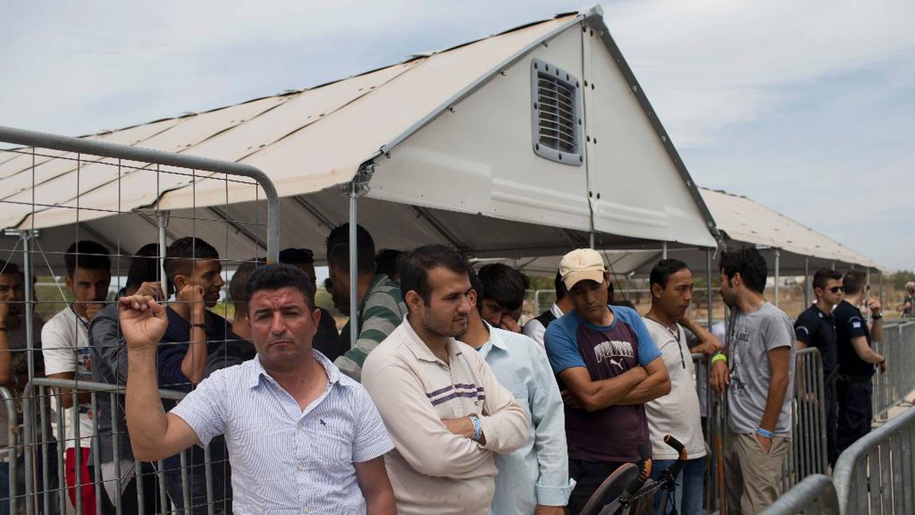 Migrants who live in the Hellenikon refugee and migrant camp of Athens wait to register for asylum on Monday, June 13, 2016. Authorities began registering applications at the site Monday, in a processes expected to last months as more than 50,000 migrants and refugees have been stranded in Greece in the wake of European border closures. (AP Photo/Petros Giannakouris)