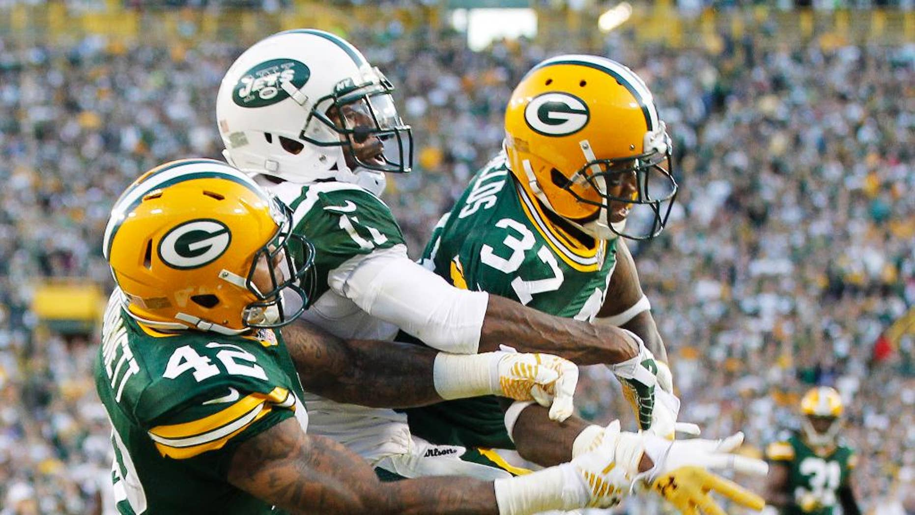 Green Bay Packers' Sam Shields (37) and Morgan Burnett break up a pass intended for New York Jets' Jeremy Kerley during the second half of an NFL football game Sunday, Sept. 14, 2014, in Green Bay, Wis. (AP Photo/Mike Roemer)