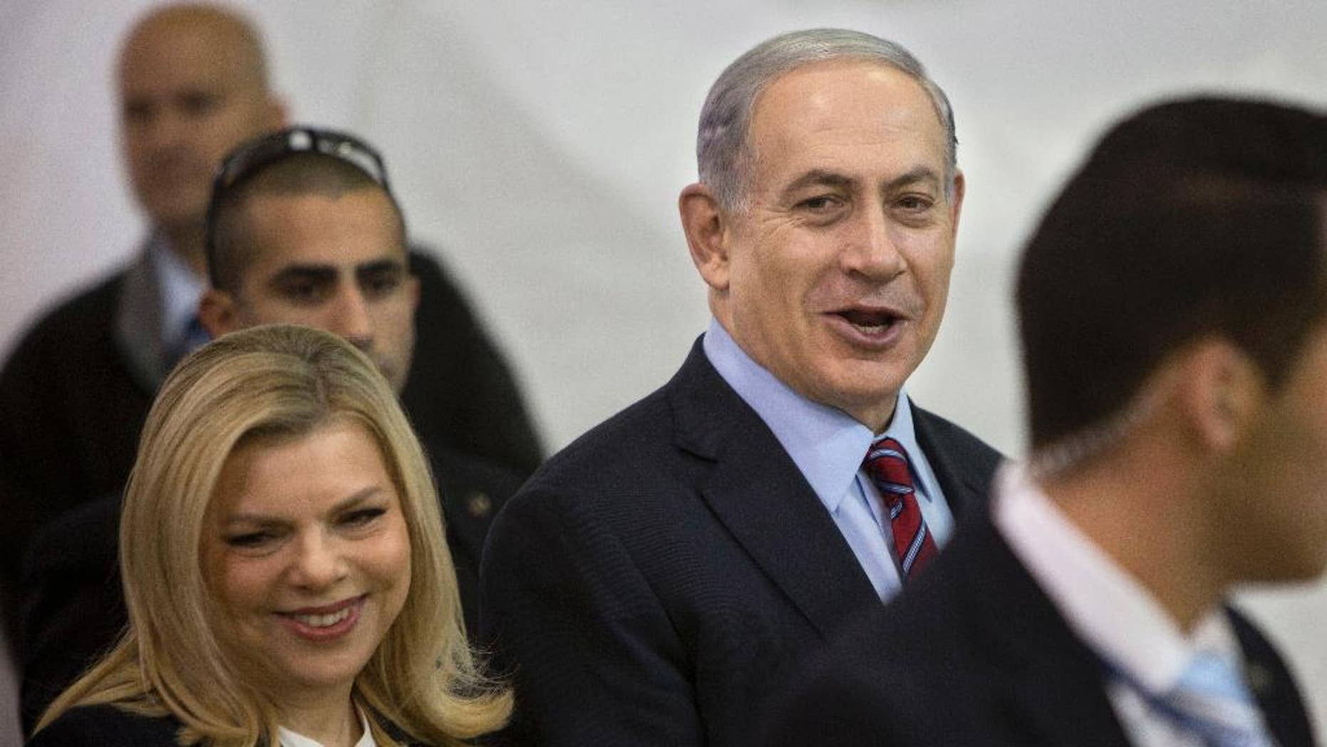 FILE - In this Wednesday, Dec. 31, 2014 file photo, Israeli Prime Minister Benjamin Netanyahu and his wife Sarah arrive for the Likud party primary elections in Jerusalem. Already under fire in Israel and abroad, Prime Minister Benjamin Netanyahu is now dealing with headaches on the home front as well following a series of scandals involving his wife. (AP Photo/Oded Balilty, File)