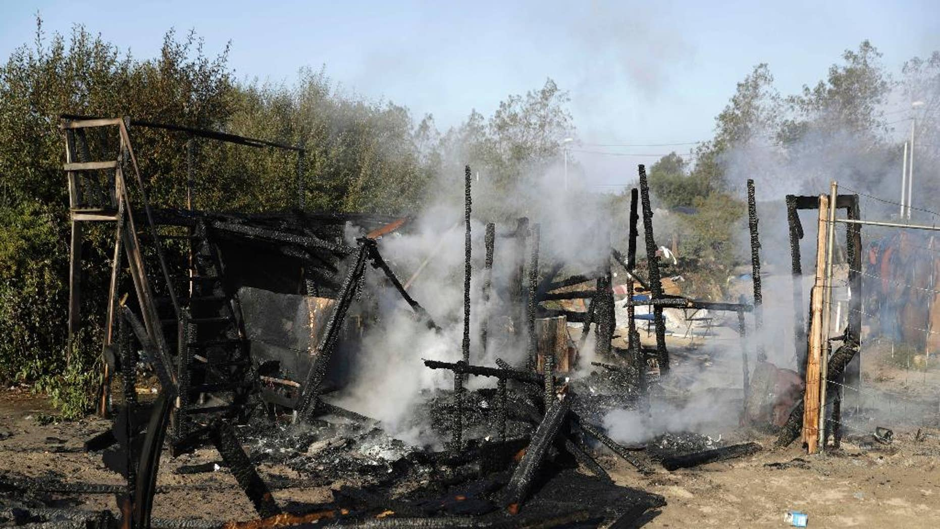 """The remains of a shelter that was set on fire Tuesday at the refugee camp known as """"The Jungle."""""""