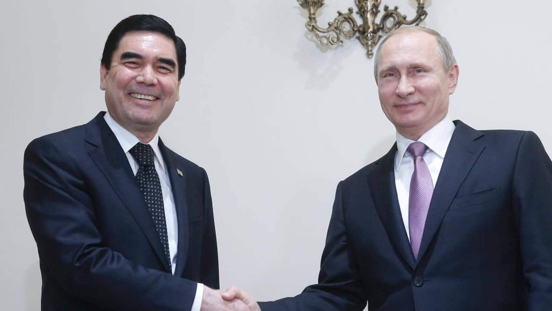 FILE- In this Nov. 23, 2015 file image, Russian President Vladimir Putin, right, shakes hands with his Turkmenistan counterpart Gurbanguly Berdymukhamedov during their meeting at the Gas Exporting Countries Forum, GECF, summit in Tehran, Iran. Lawmakers in the Central Asian nation of Turkmenistan have adopted Wednesday 14 September amendments to the country's constitution, paving the way for a life-long presidency for the incumbent leader Gurbanguly Berdymukhamedov. (Sergei Chirikov/Pool photo via AP file)