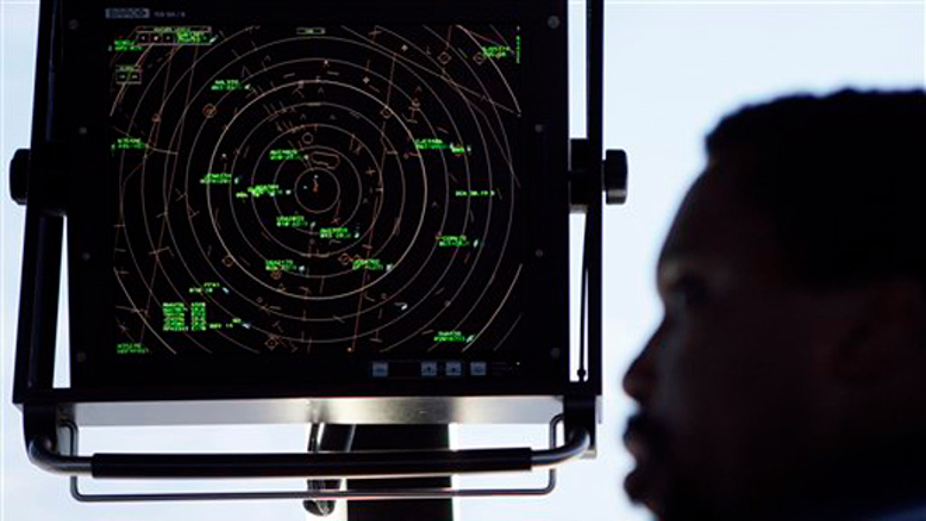 In this Sept. 18, 2008, file photo an air traffic controller stands beneath a radar screen in the control tower at Washington's Reagan National Airport.