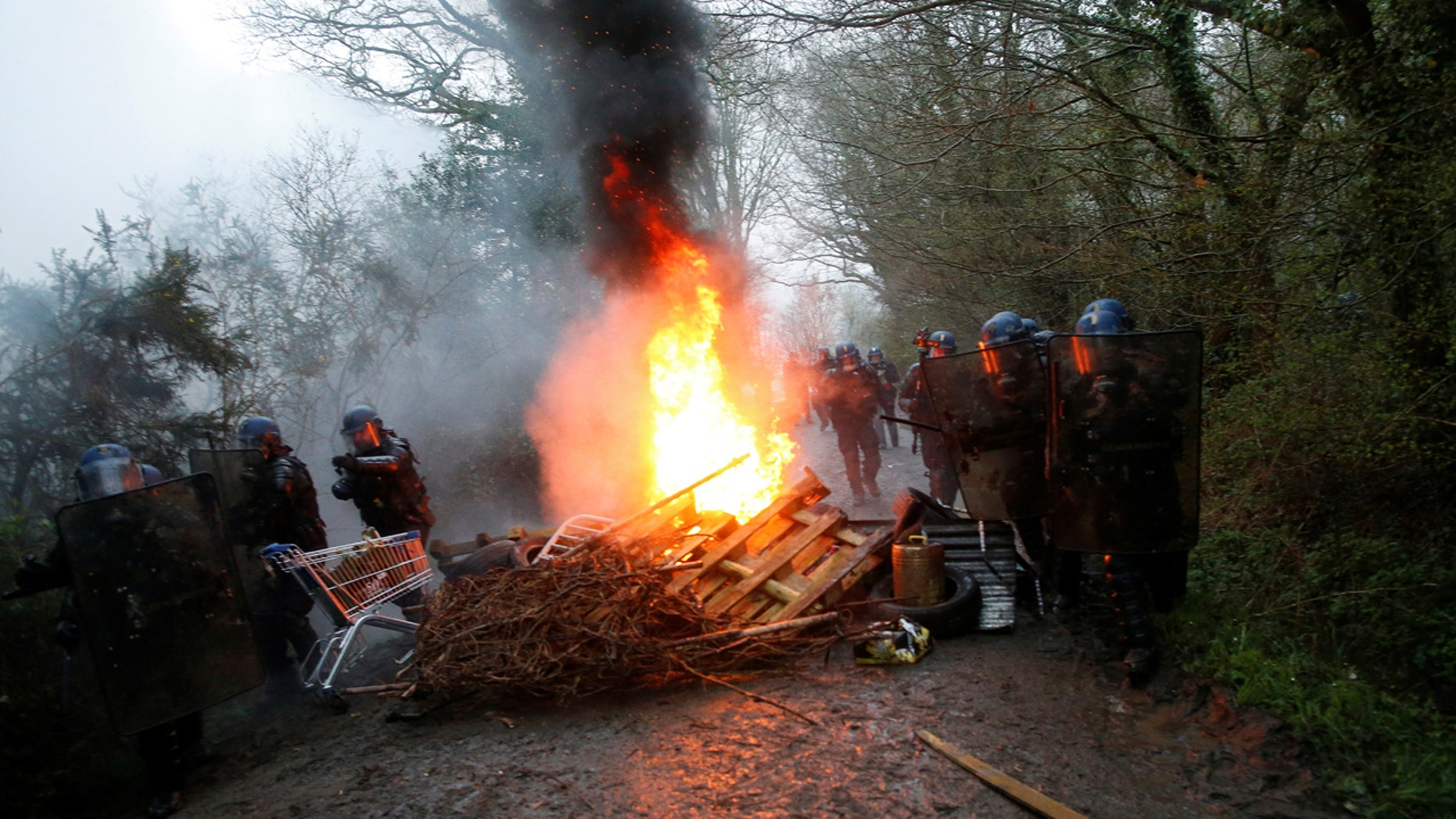 French gendarmes stand near burning debris on a road during an evacuation operation in Notre-Dame-des-Landes, near Nantes, France.
