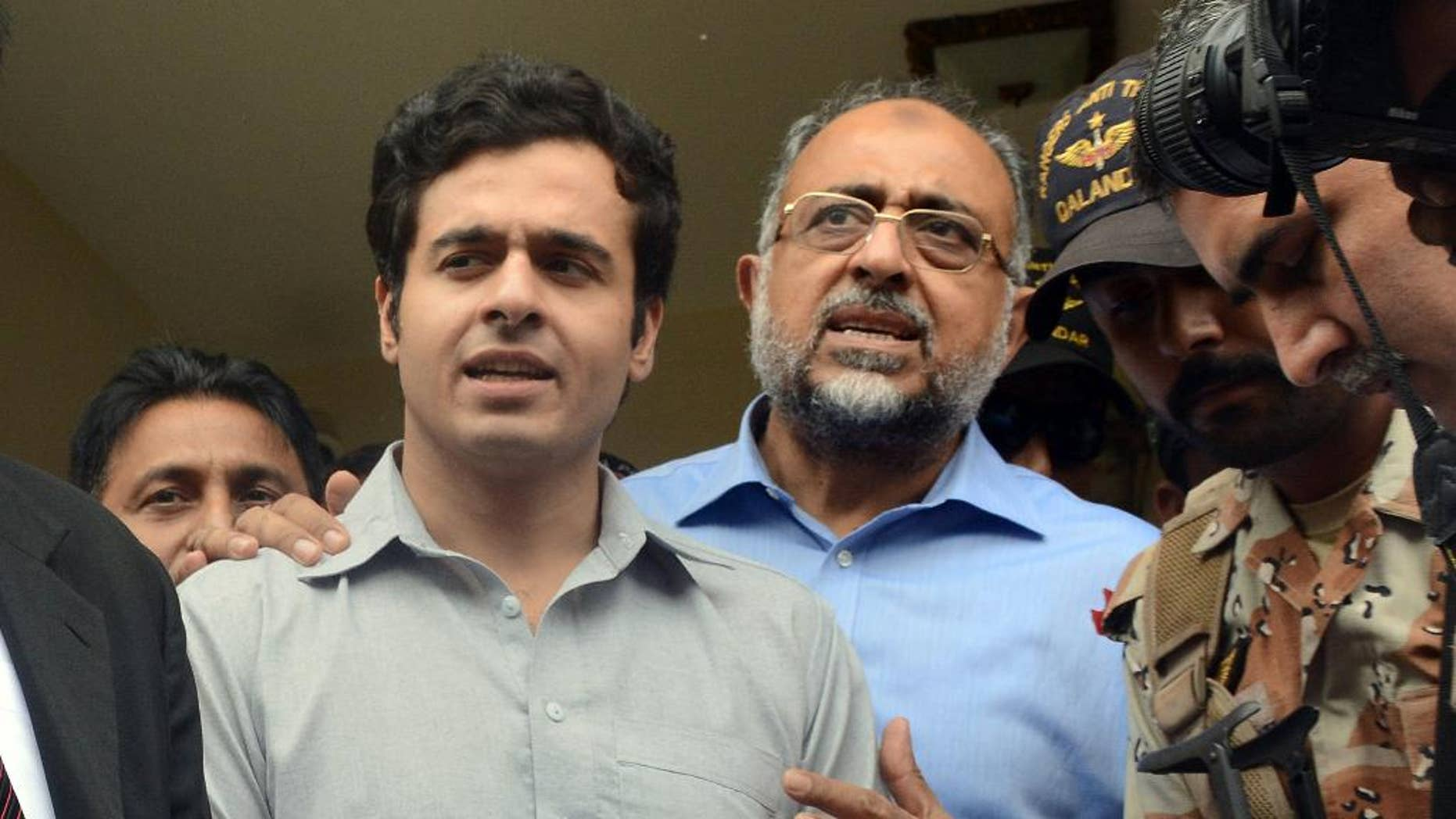 Awais Shah, center left, speaks to journalists with his father Sajjad Ali Shah, center right, chief justice of Sindh's High Court, after the son was rescued from kidnappers.
