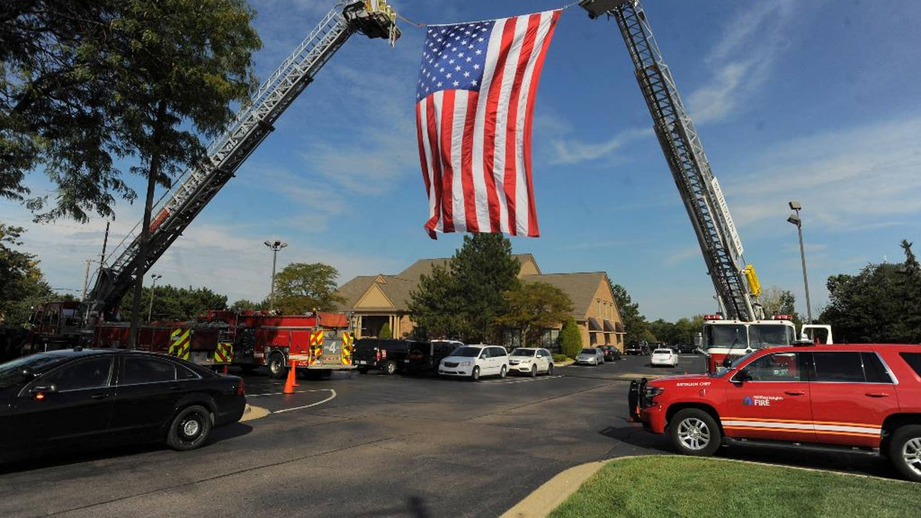 A large American flag is unfurled by Sterling Heights and Washington Twp. Fire Departments as mourners begin to arrive for visitation for Detroit Police officer Ken Steil in Sterling Heights, Mich., Wednesday Sept. 21, 2016.  Steil died unexpectedly Saturday of a blood clot, five days after being shot in the shoulder.  (Steve Perez/Detroit News via AP)
